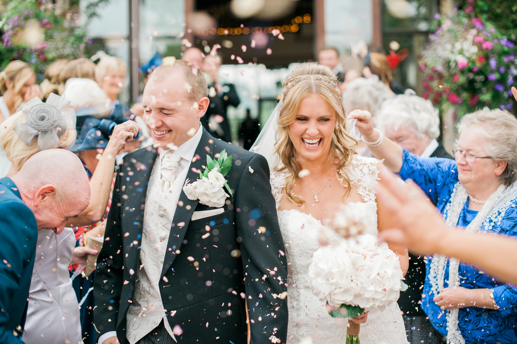 Bride and groom walking as guests throw confetti over them