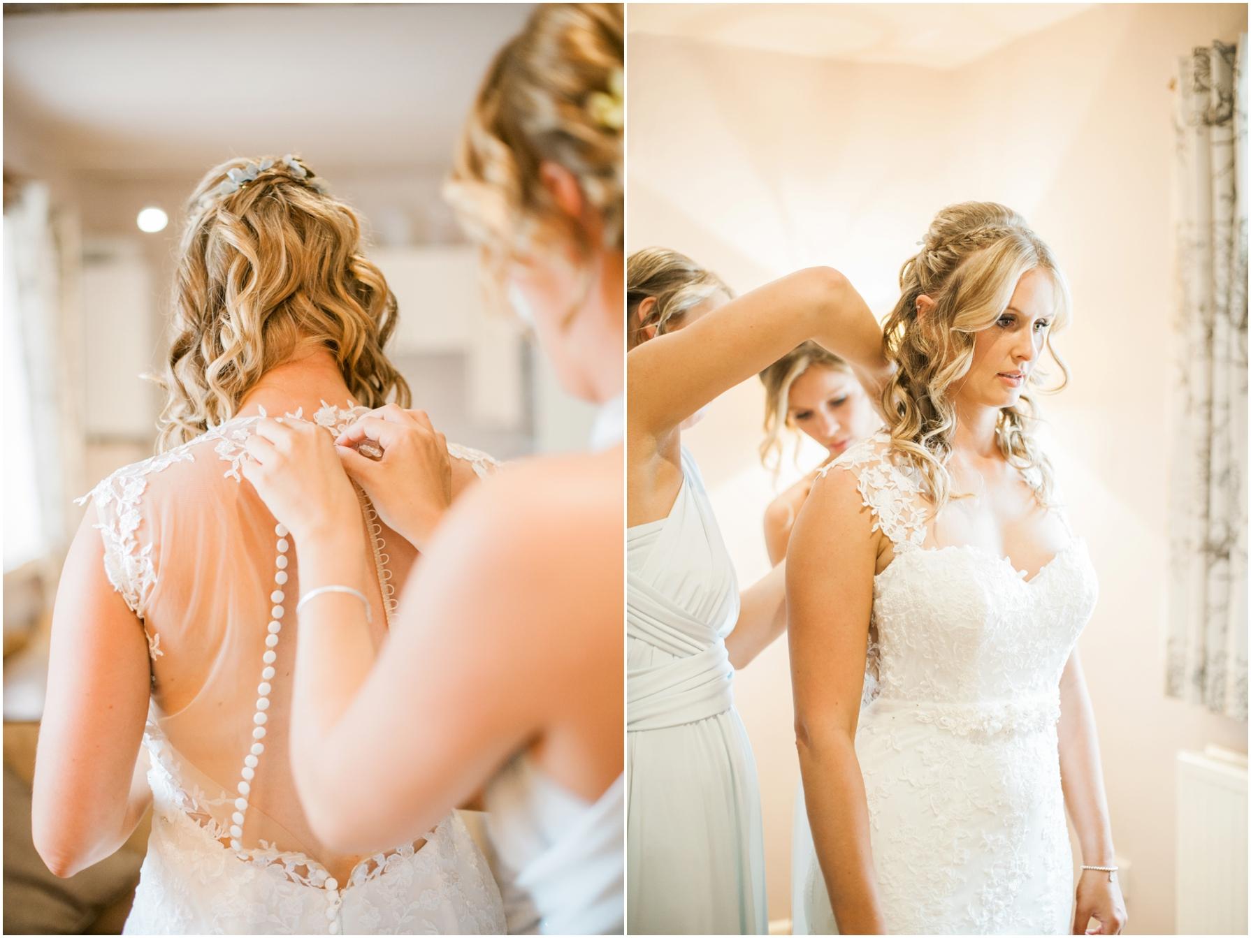 bridesmaid helping bride into her dress