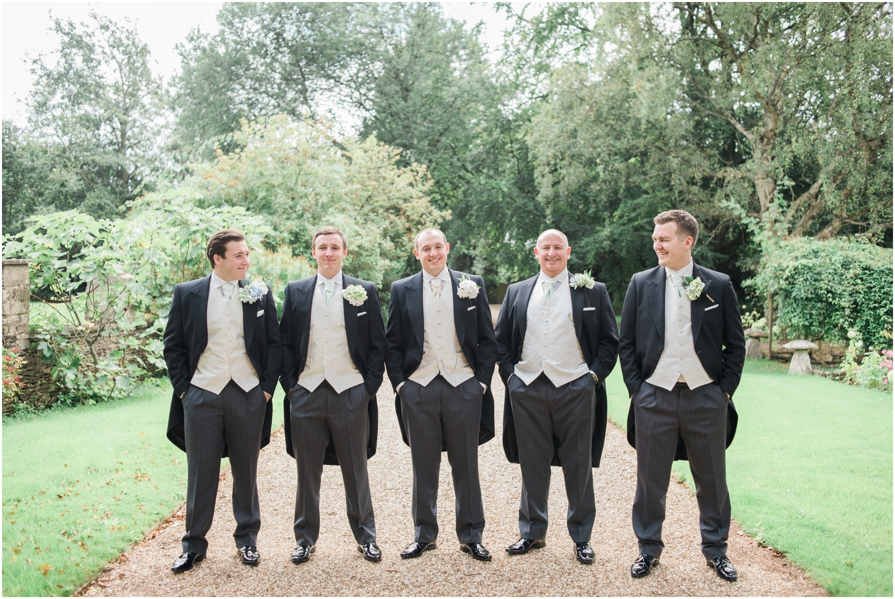 formal portrait of the Groom and groomsmen on the driveway outside the great the barn