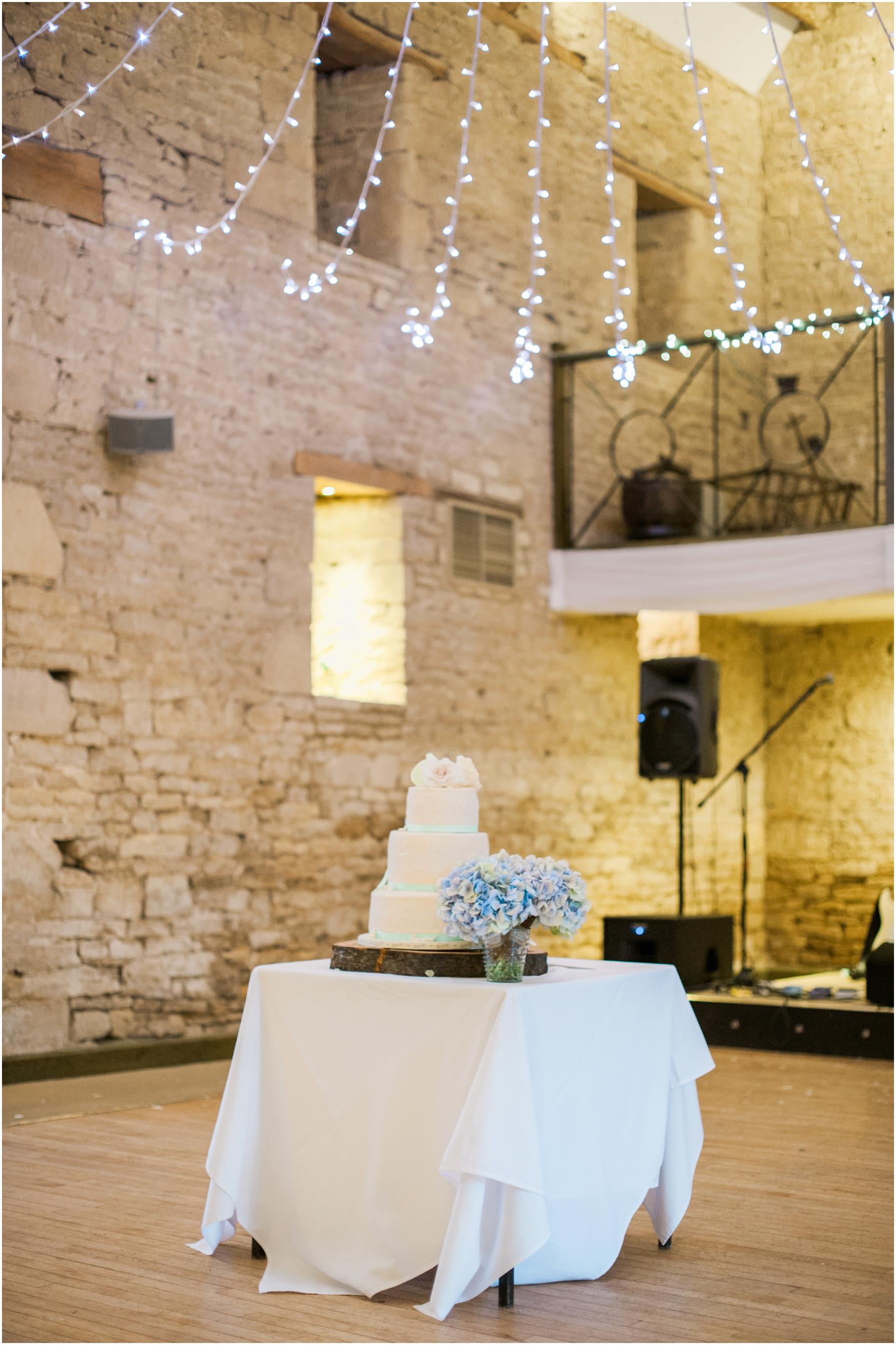 white wedding cake in a dimly lit barn