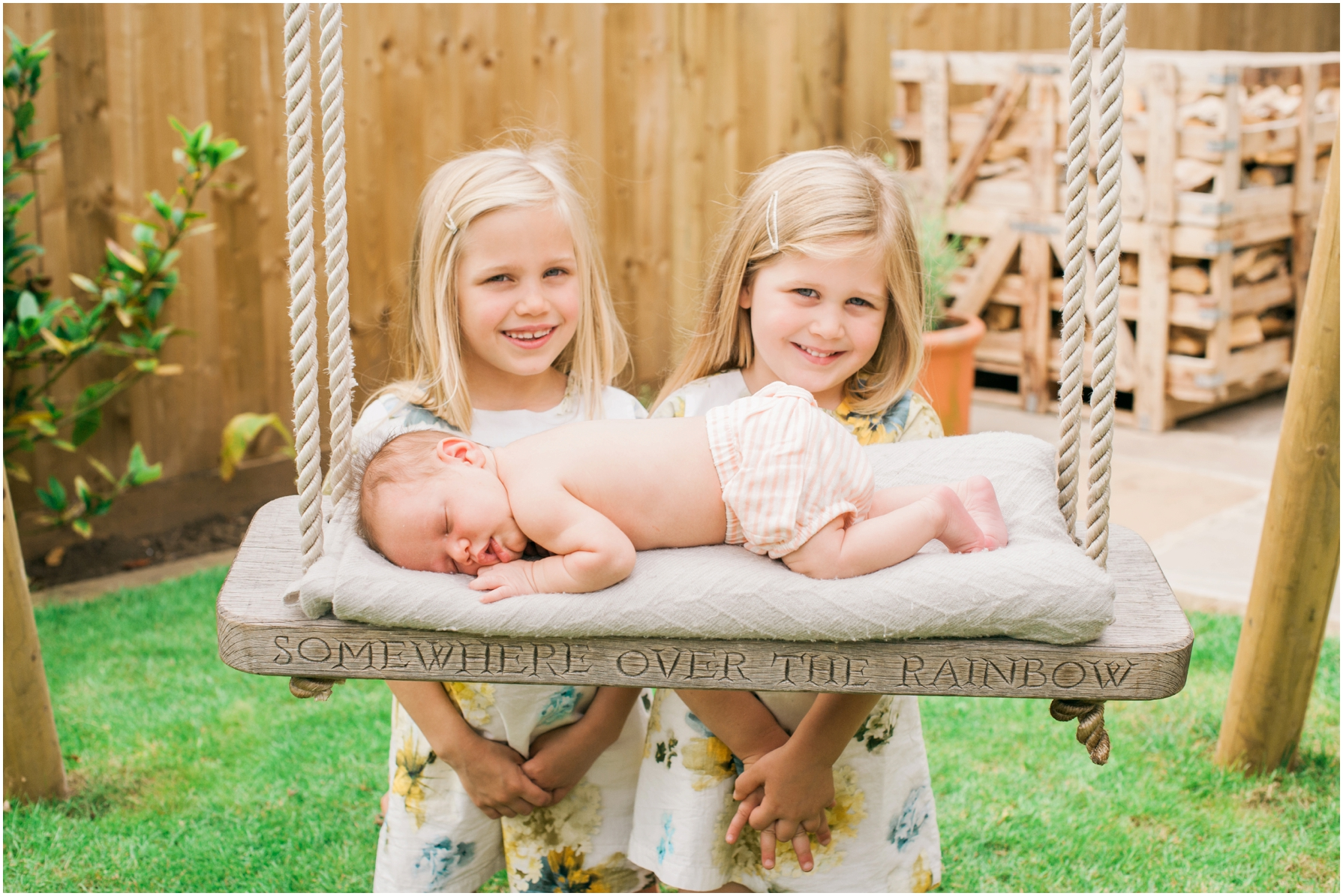two little girls pose next to their baby sister sleeping on a wooden swing