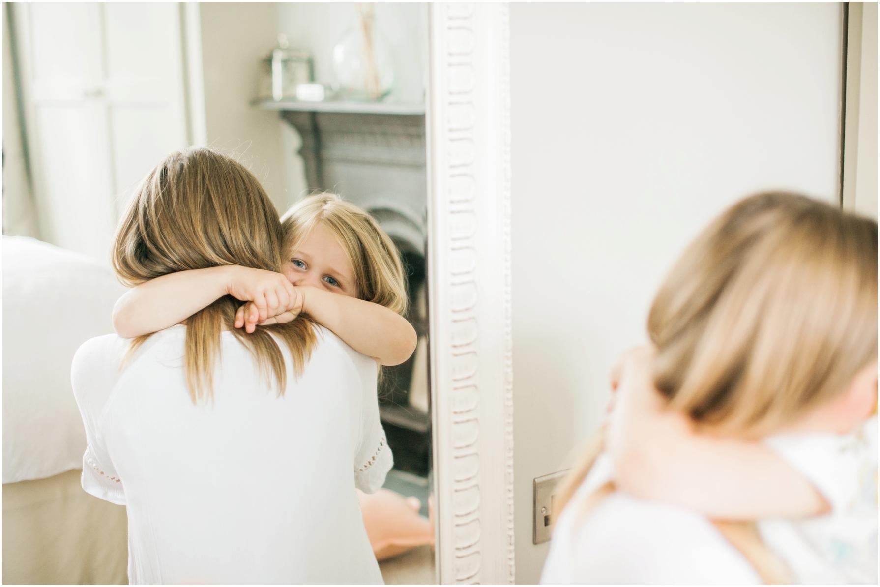 a little girl cuddling her mother