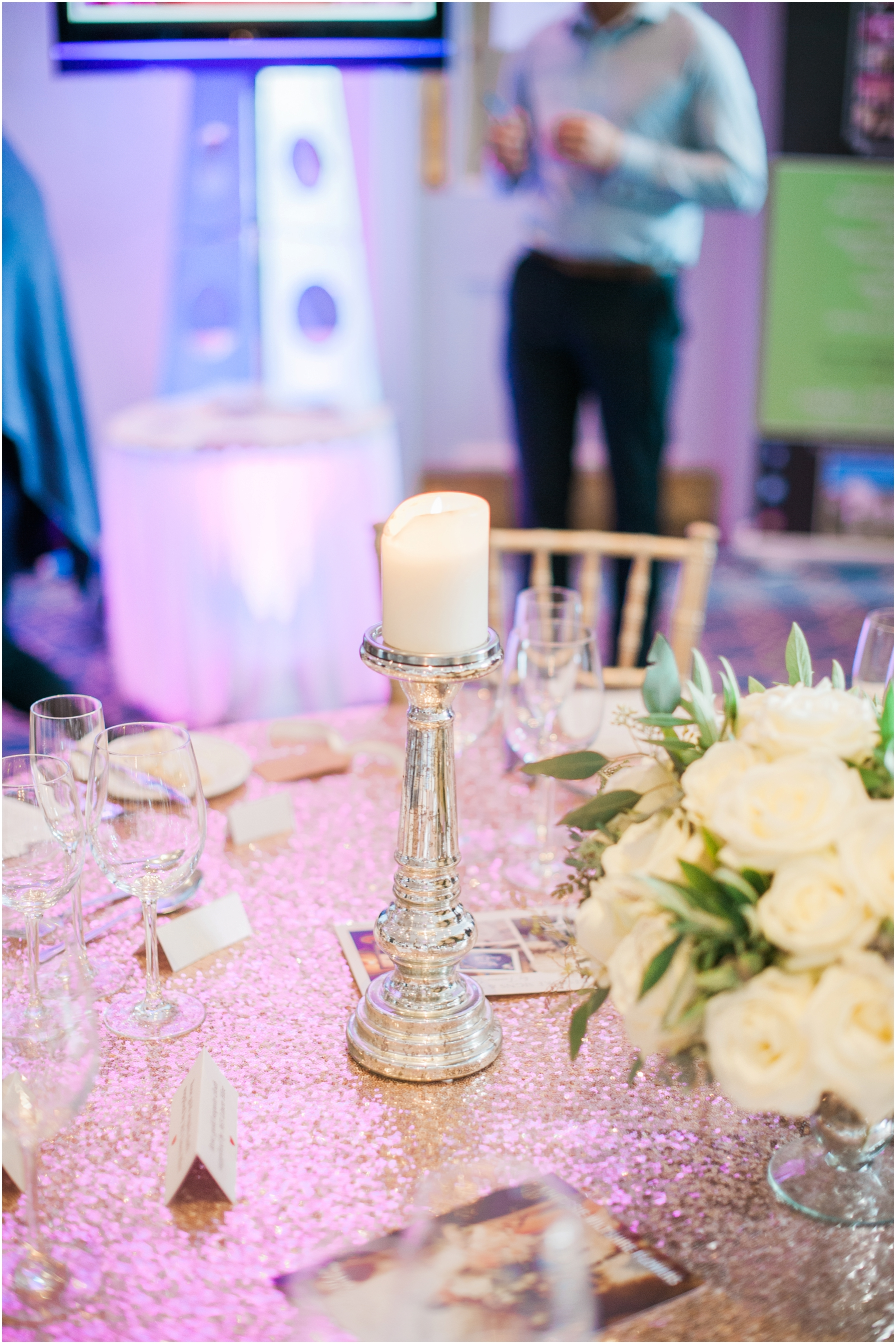 wedding breakfast table with tall pillar candles and a gold table cloth