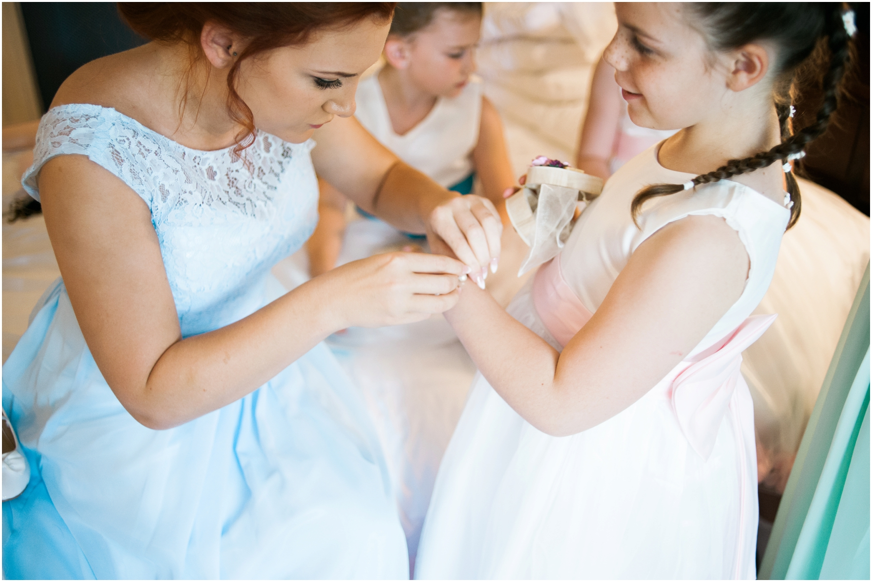 bridesmaid helping the flower girl put her jewellery on