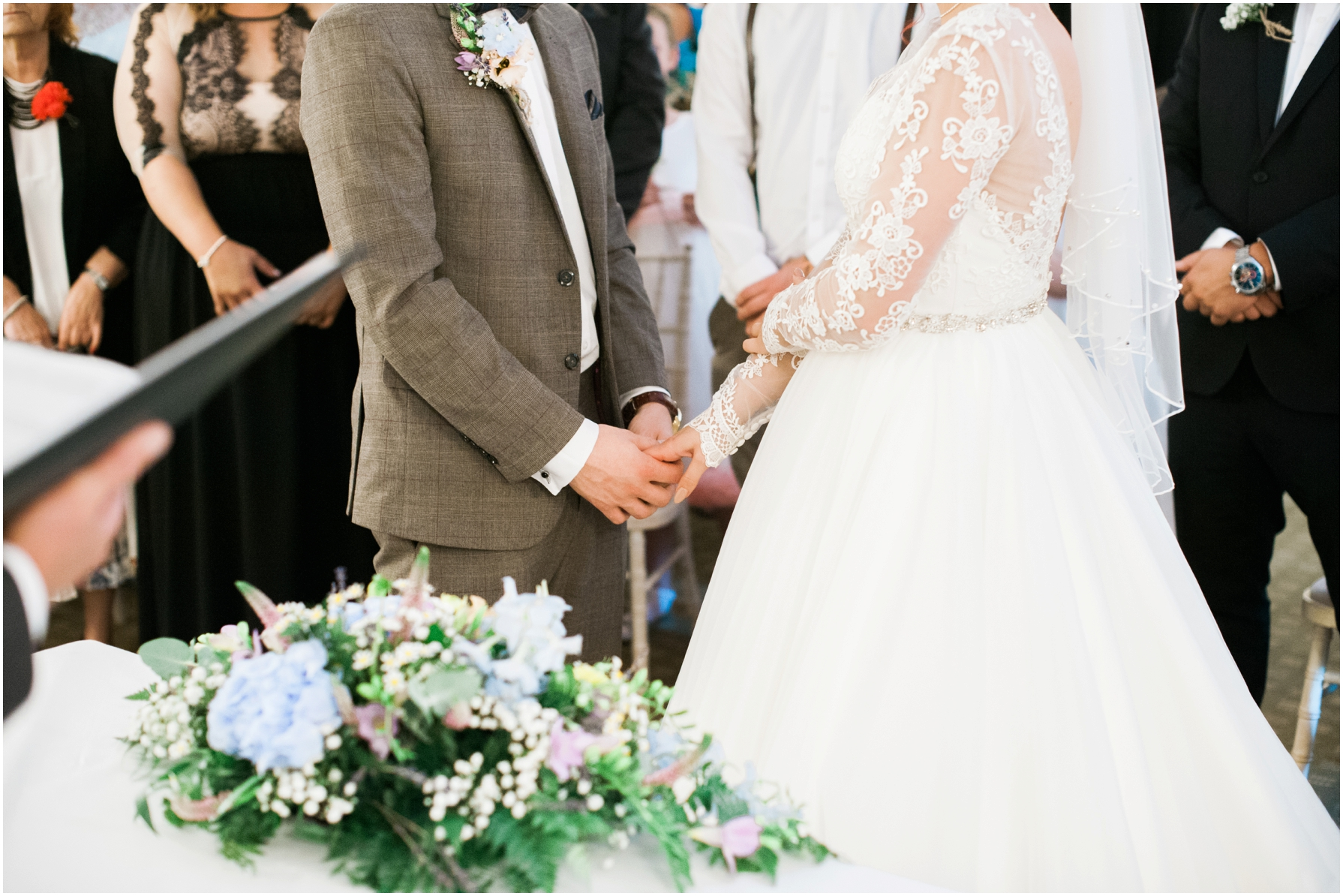 bride and groom hold hands whilst saying their vows at stratton house hotel