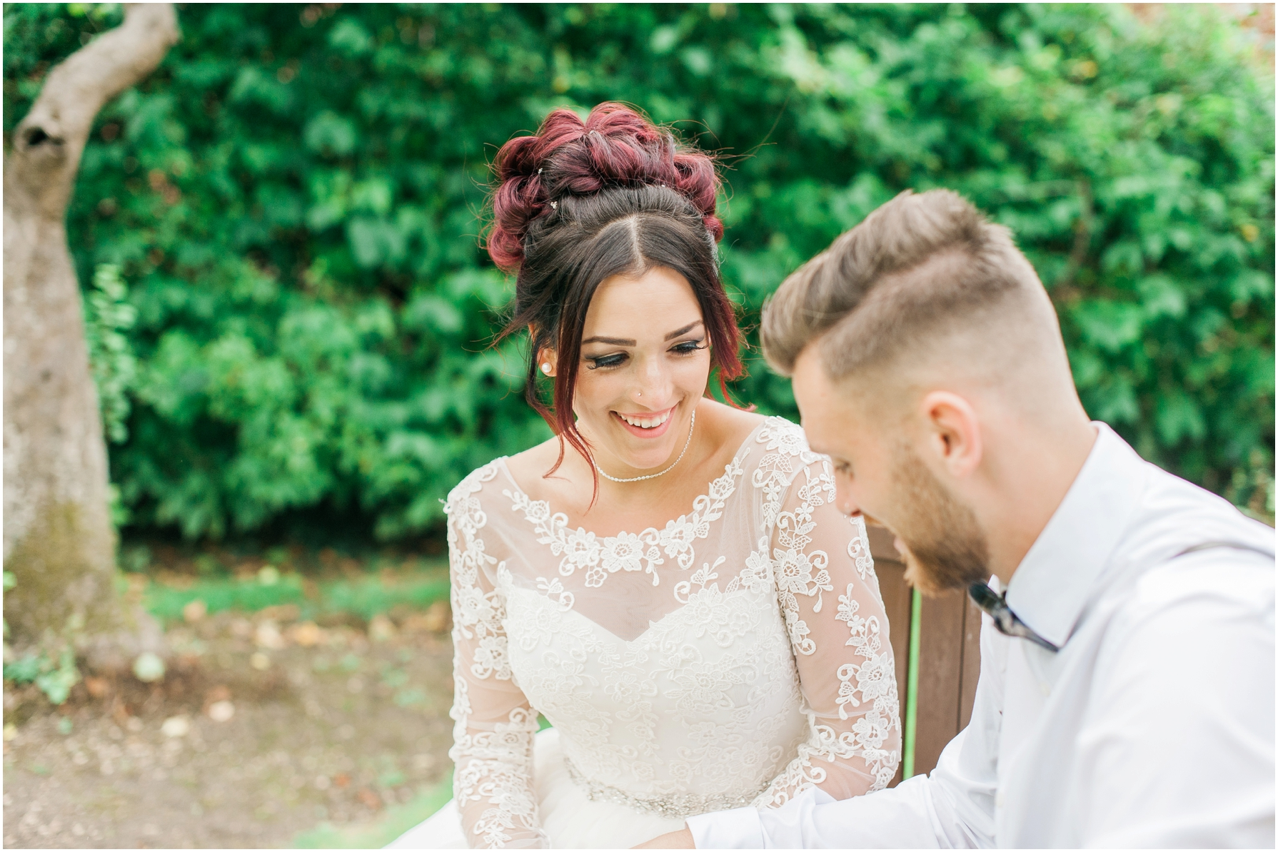 bride and groom siting on a bench looking at each other