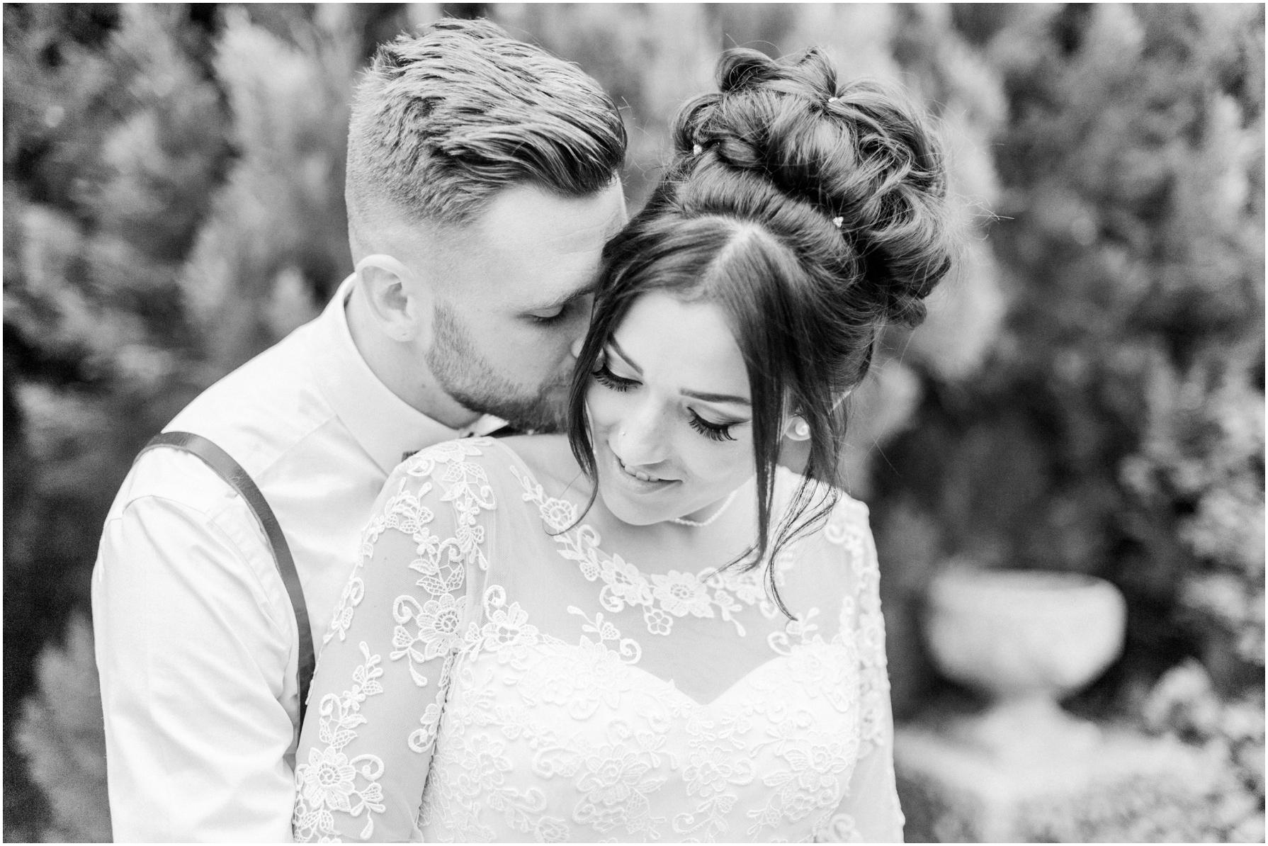 groom kissing his bride on her cheek