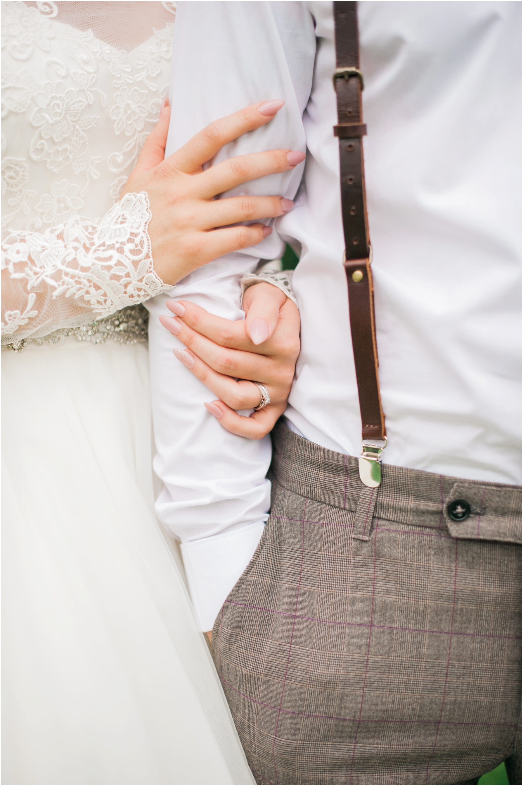 brides hands linked through grooms arms