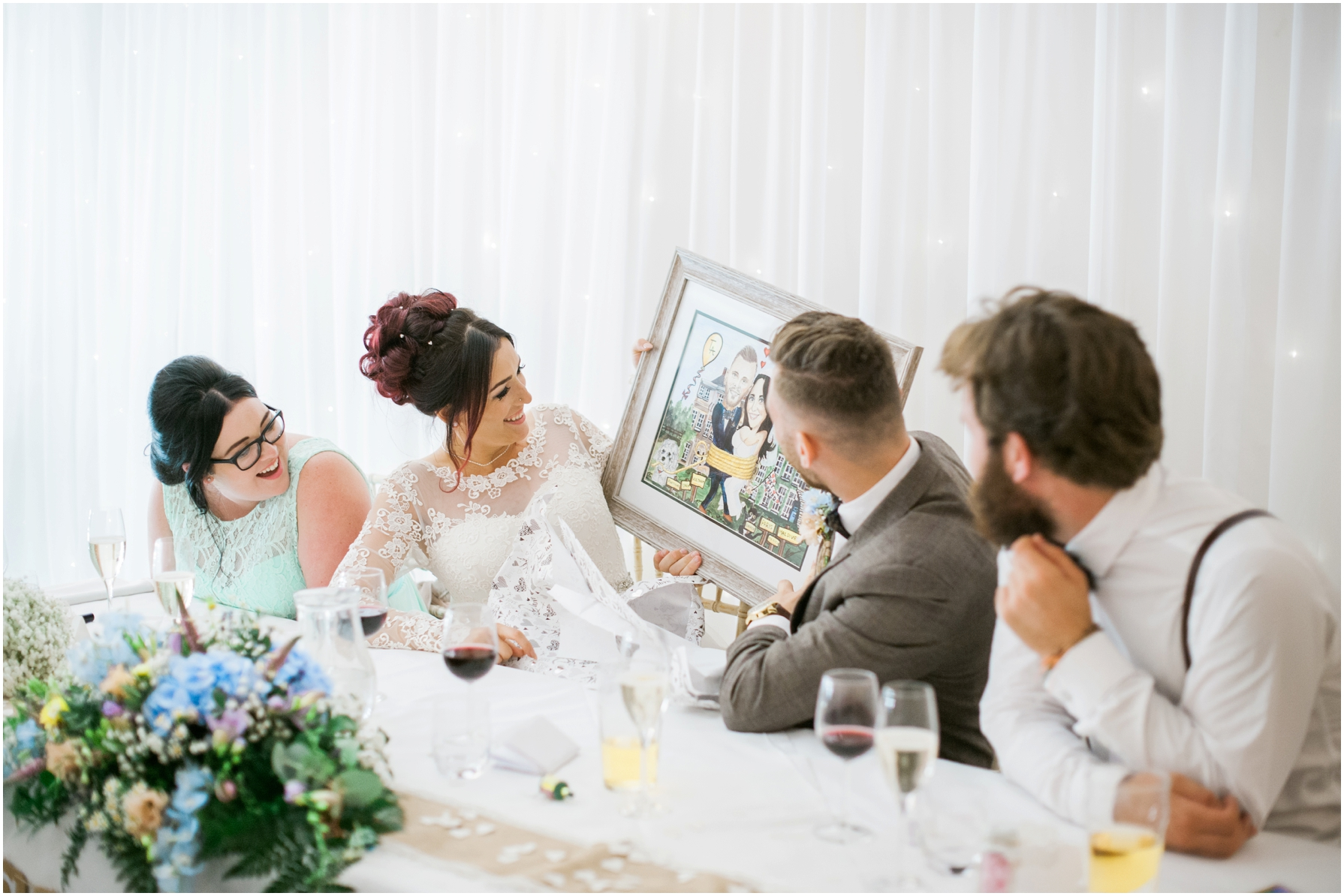 bride and groom opening a gift during the wedding speeches