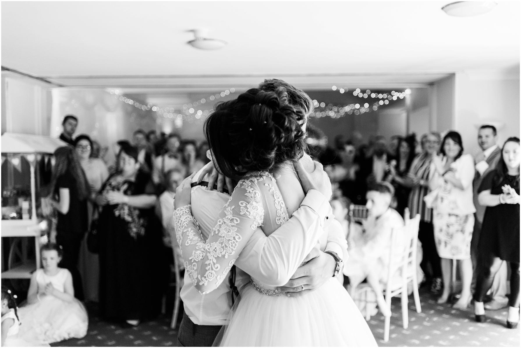 black and white image of bride and groom dancing