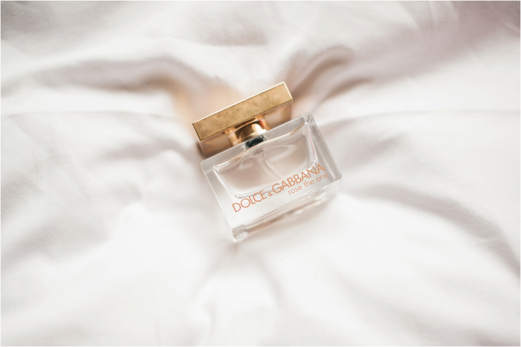 brides perfume bottle laid out on a white bed sheet
