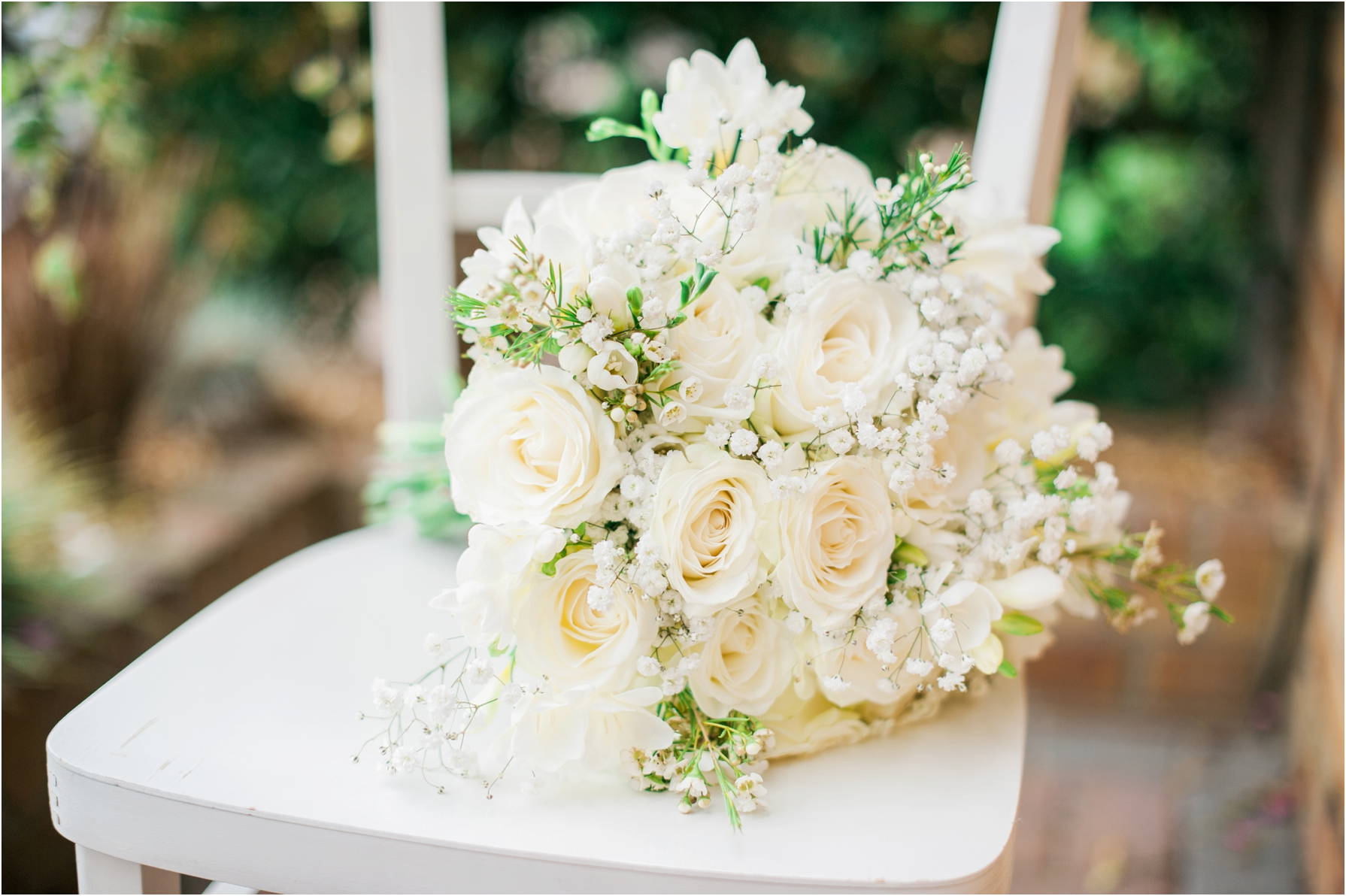 all white flower bridal bouquet on a white chair