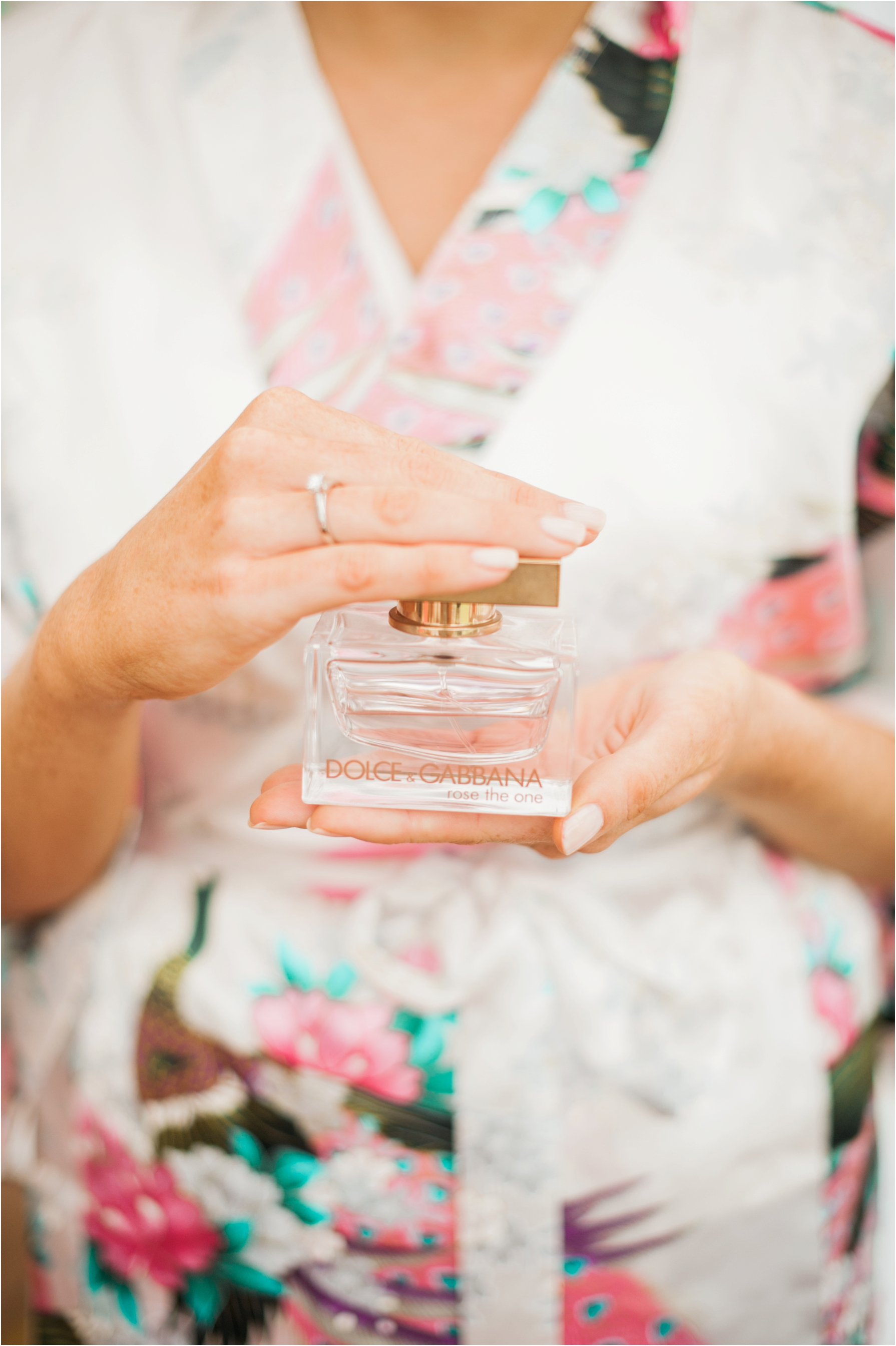 bride holding a bottle of perfume whilst she gets ready