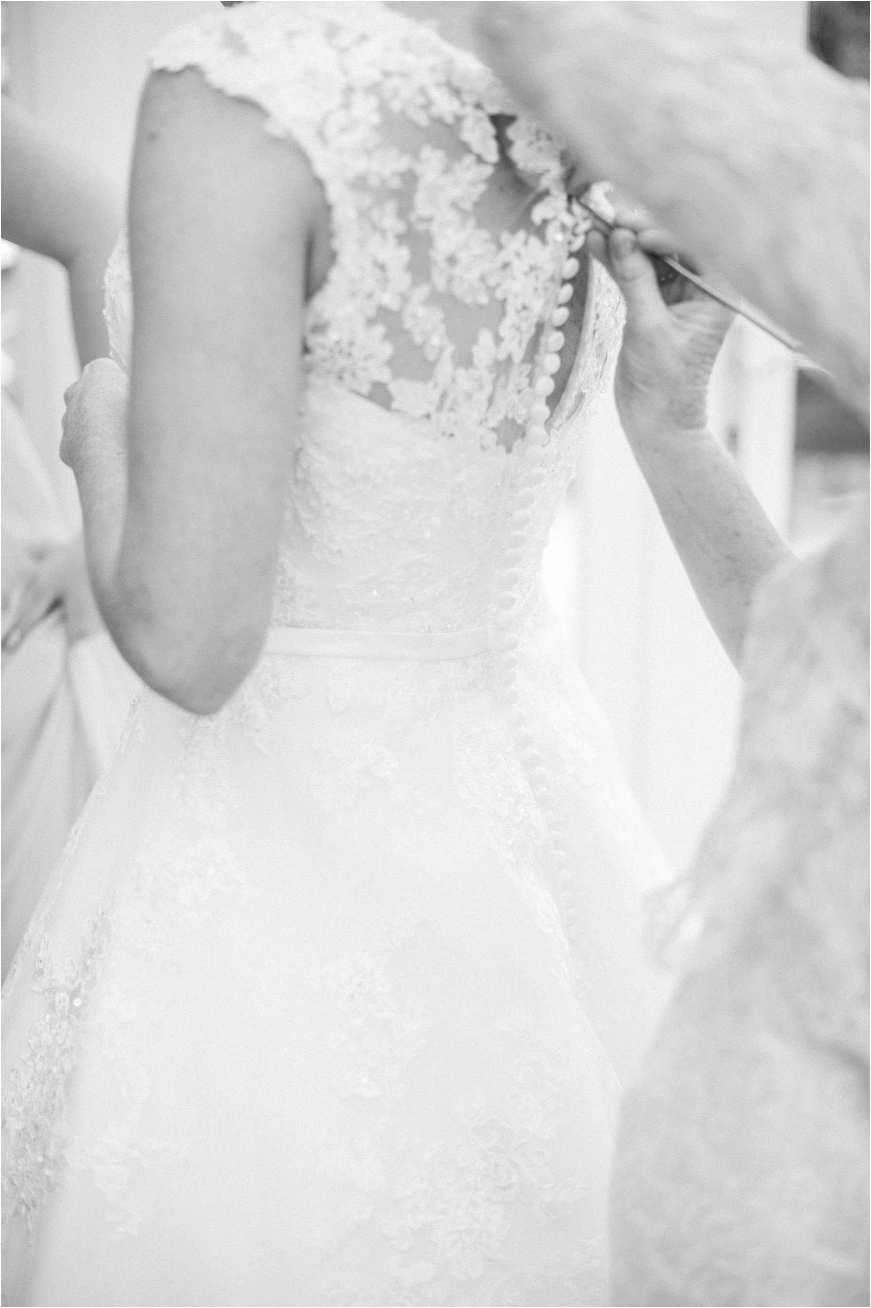 bride having her dress done up by her mother