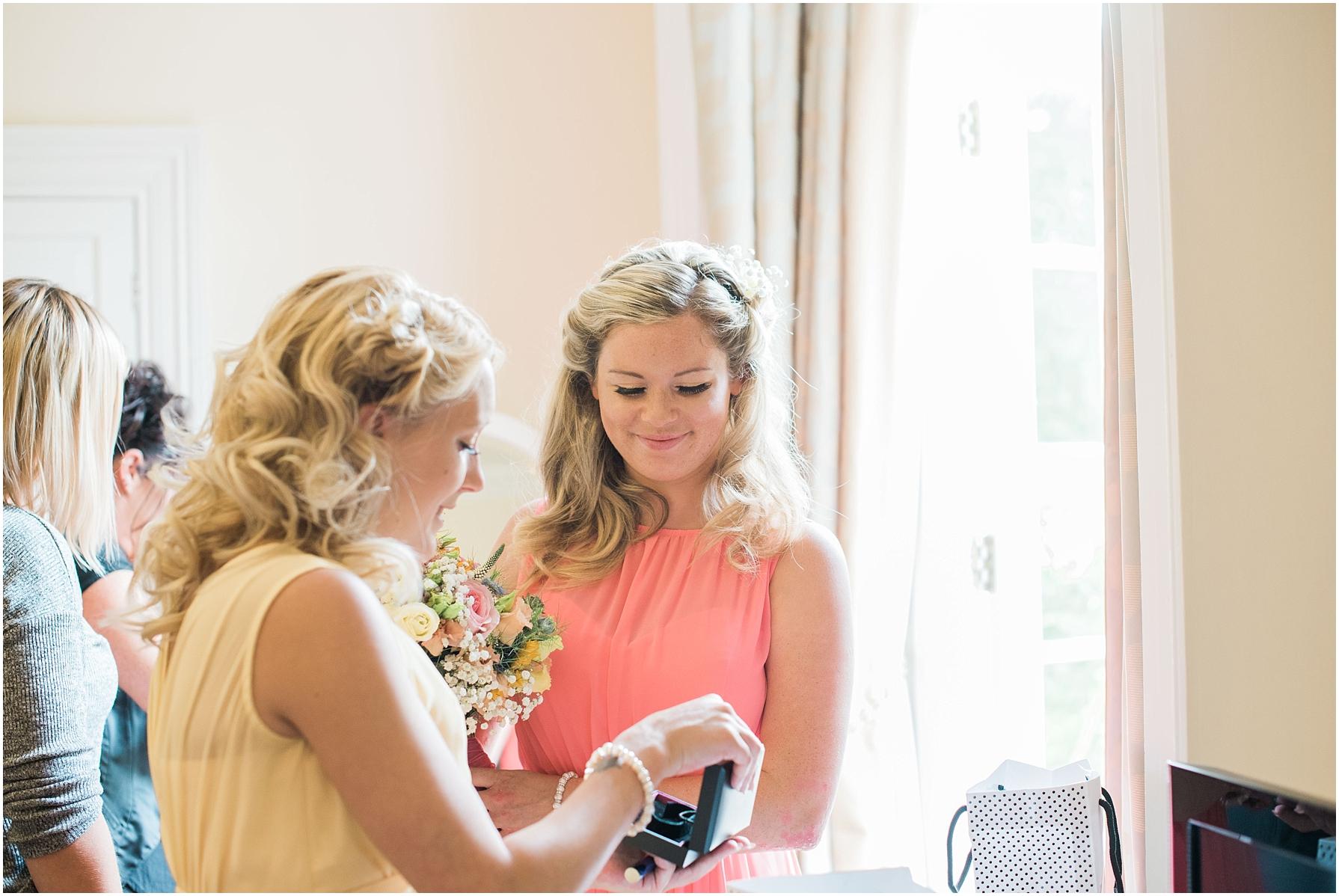bridesmaids wearing pastel dresses looking at jewellery