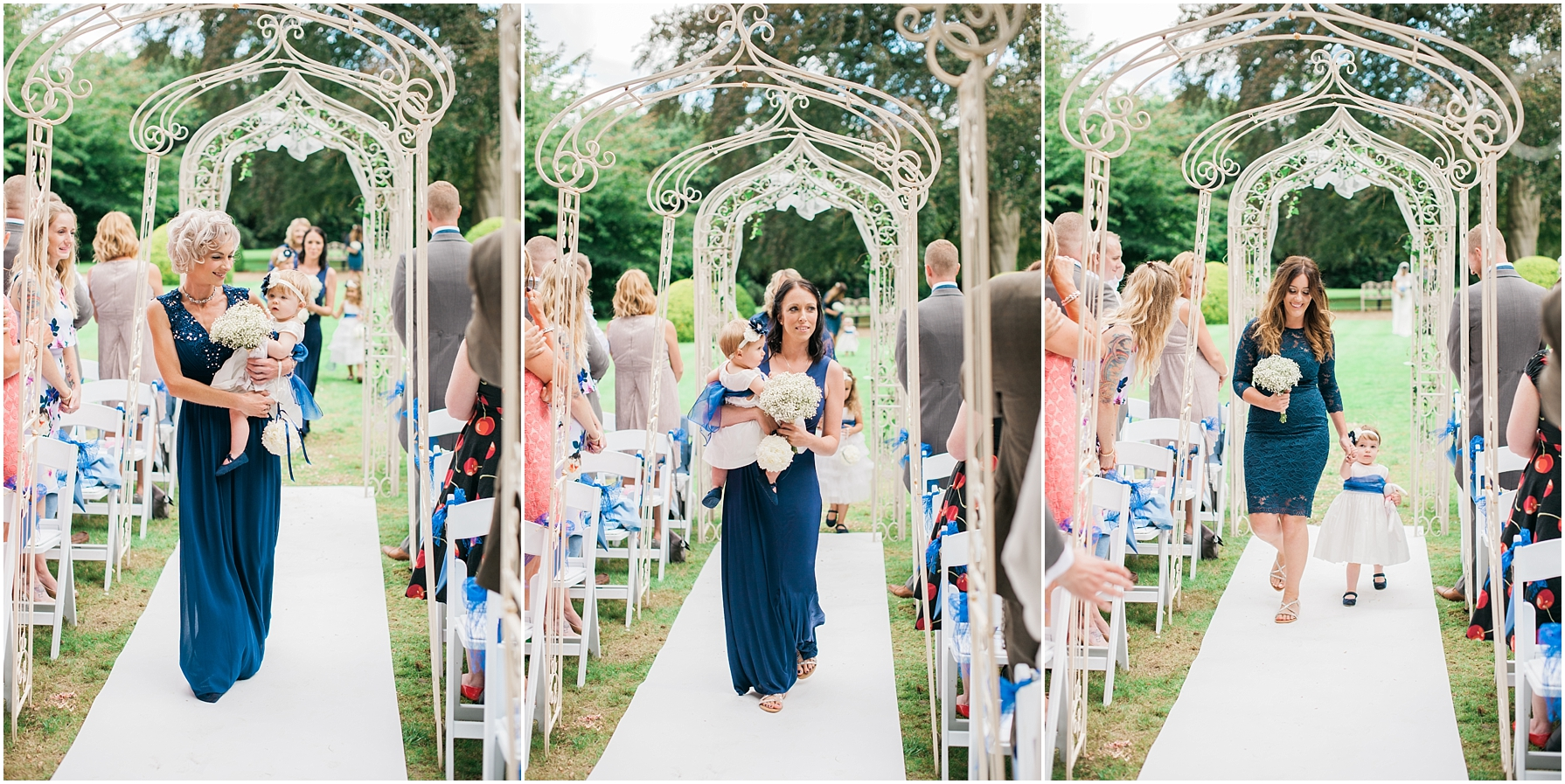bridesmaids walking up the aisle wearing navy blue