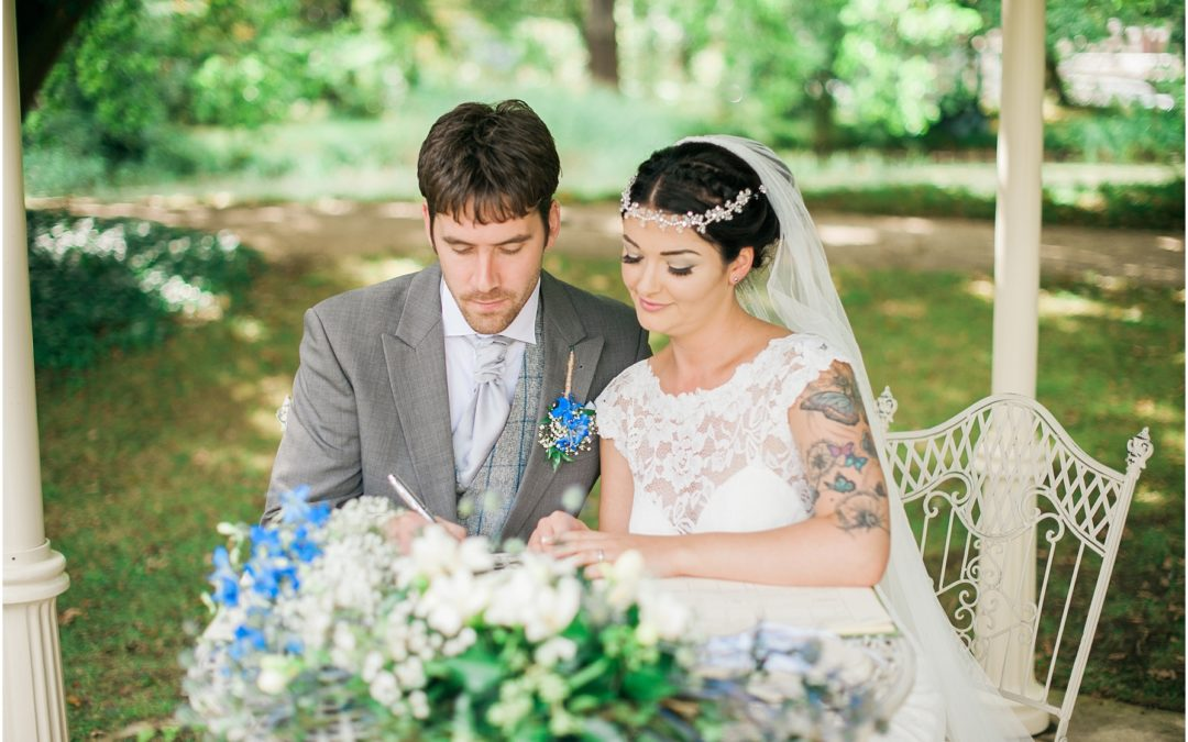 bride and groom signing the register outside at manor by the lake