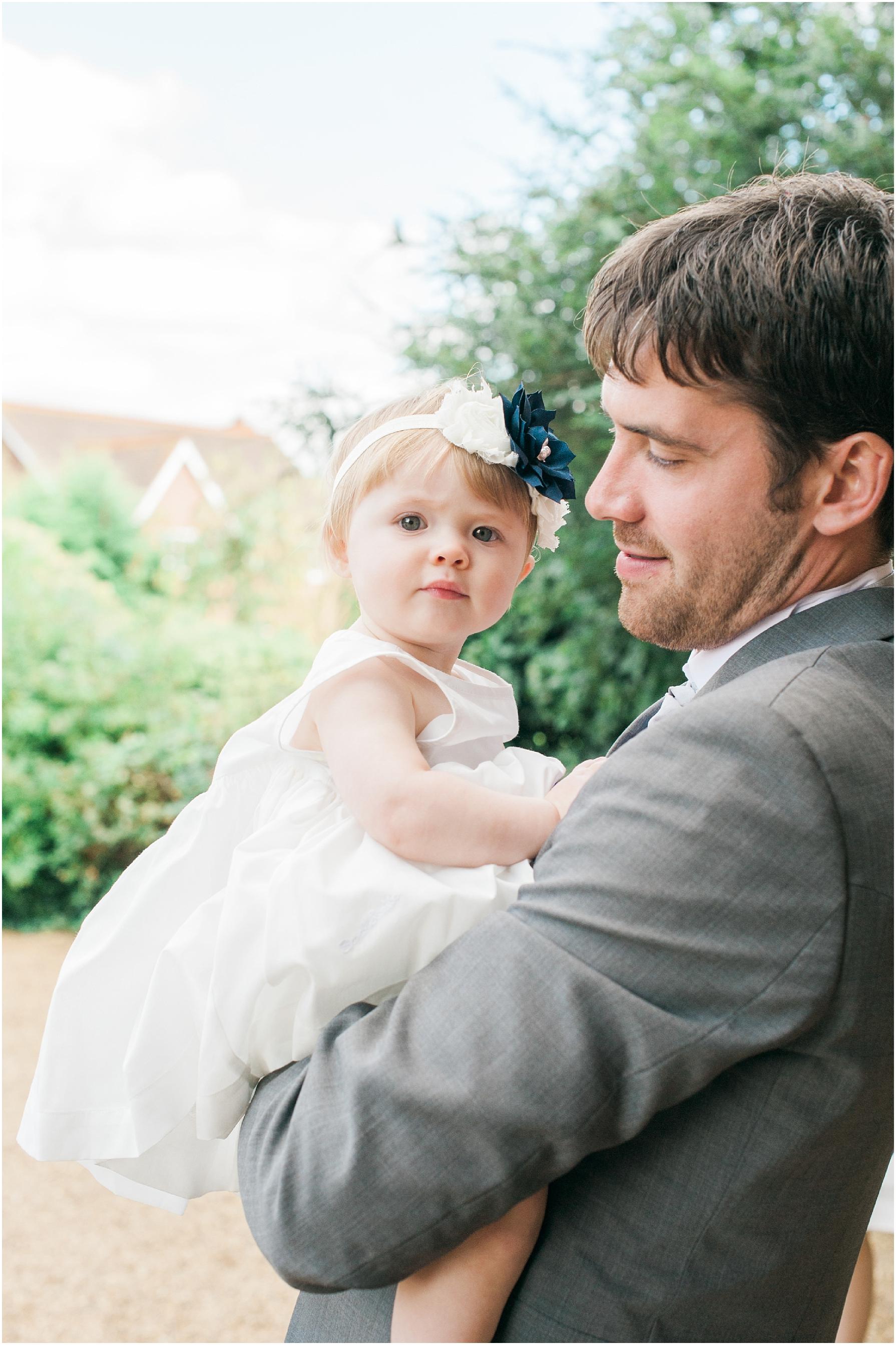 groom holding his little girl