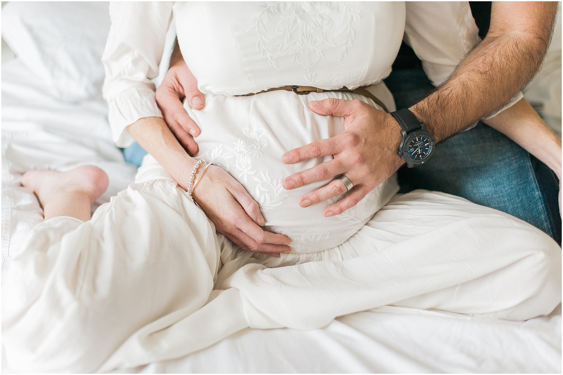 man's hands on his partners pregnant belly