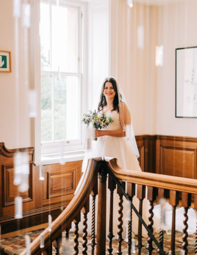bride standing at the top of the stairs at cowley manor