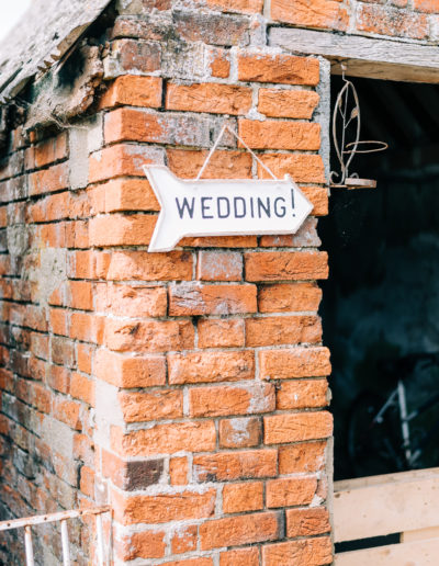 hand made wedding sign hanging outside a barn