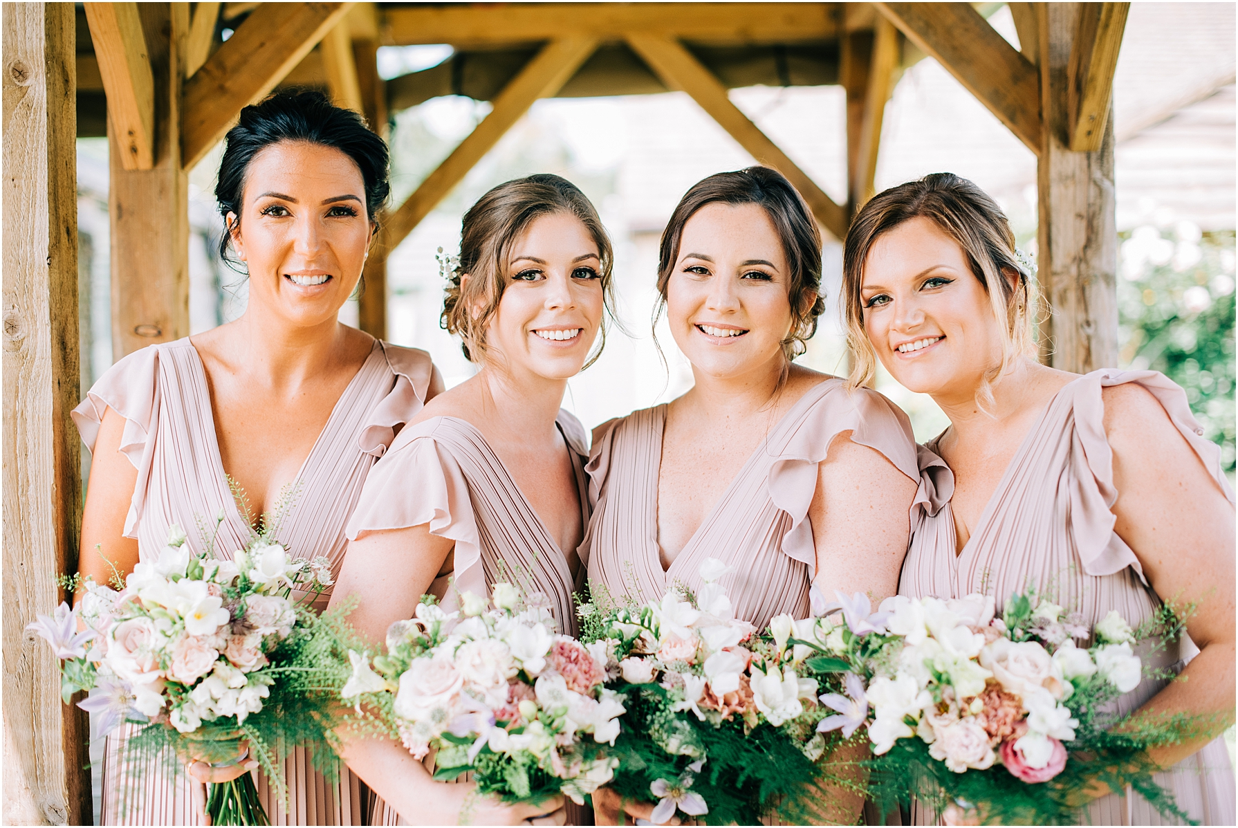 four bridesmaids in a row wearing pale pink dresses and holding bouquets