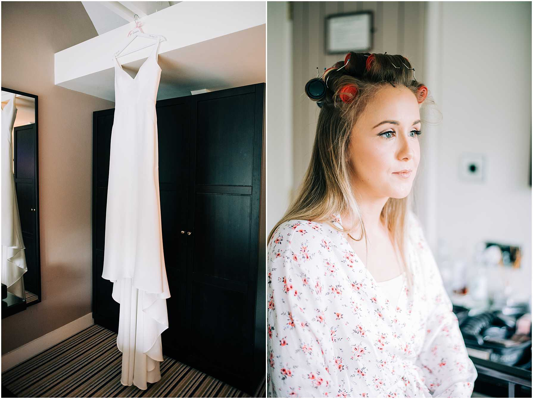 bride with rollers in her hair and wedding dress hanging up in bridal suite
