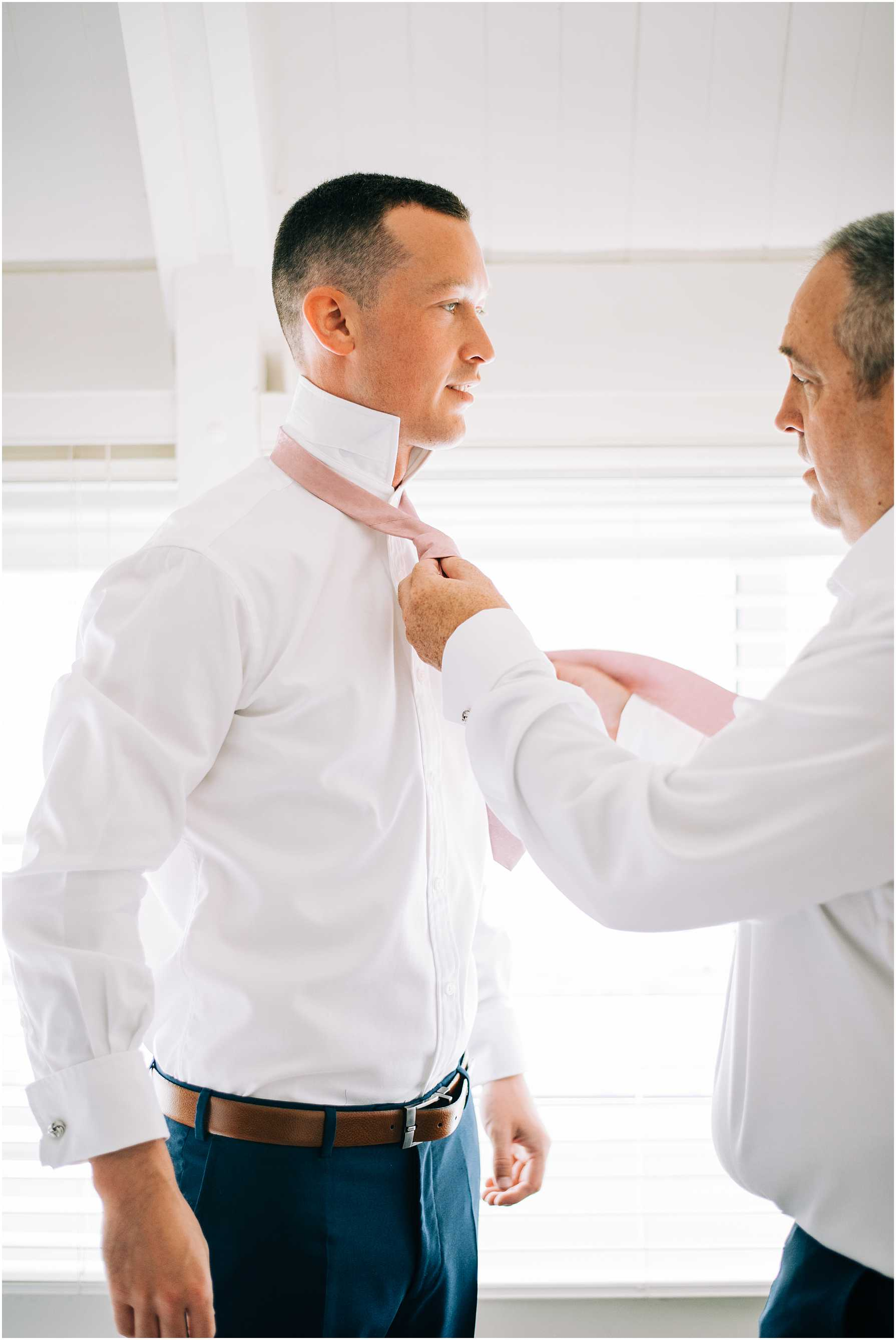 groom having his tie put on by father