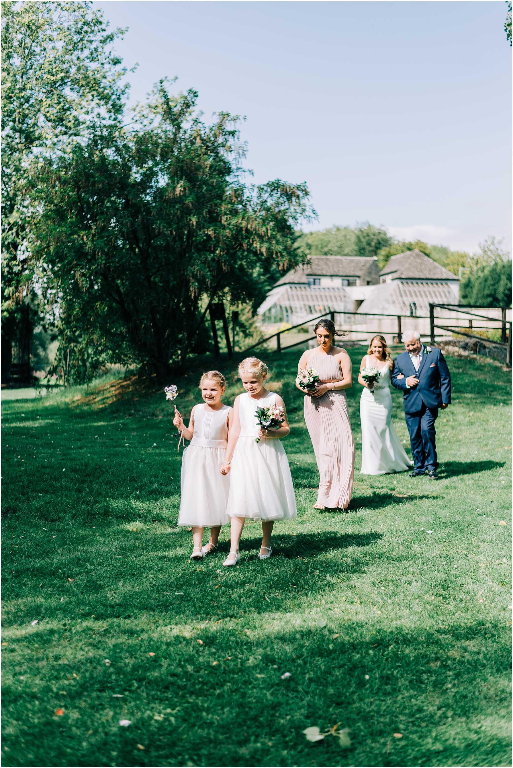 bride and bridesmaids walking on the grass to meet groom