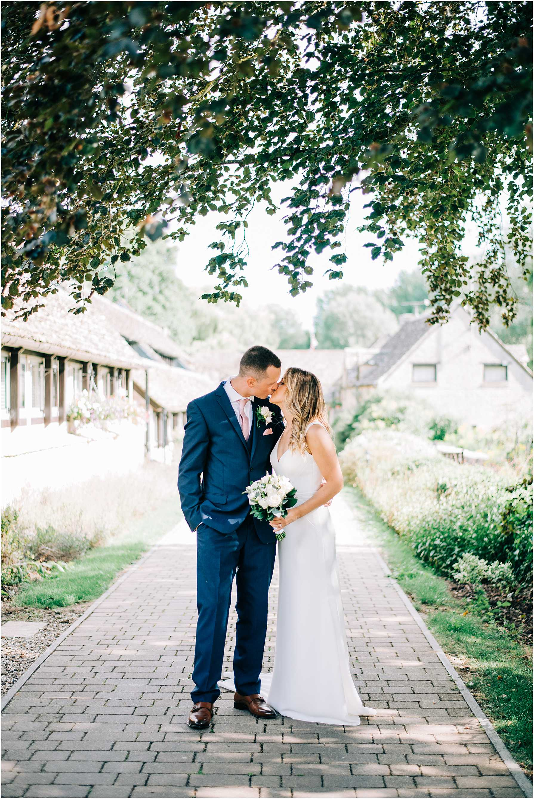 bride and groom kissing under a big tree