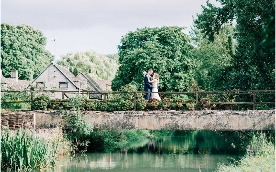 bride and groom standing on the bridge at the old swan and minster mill
