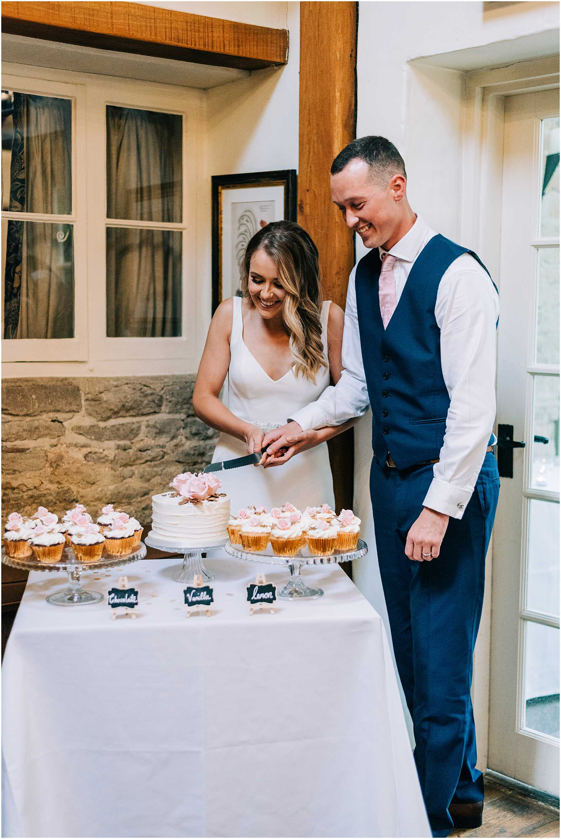 bride and groom cutting the cake at the old swan and minster mill