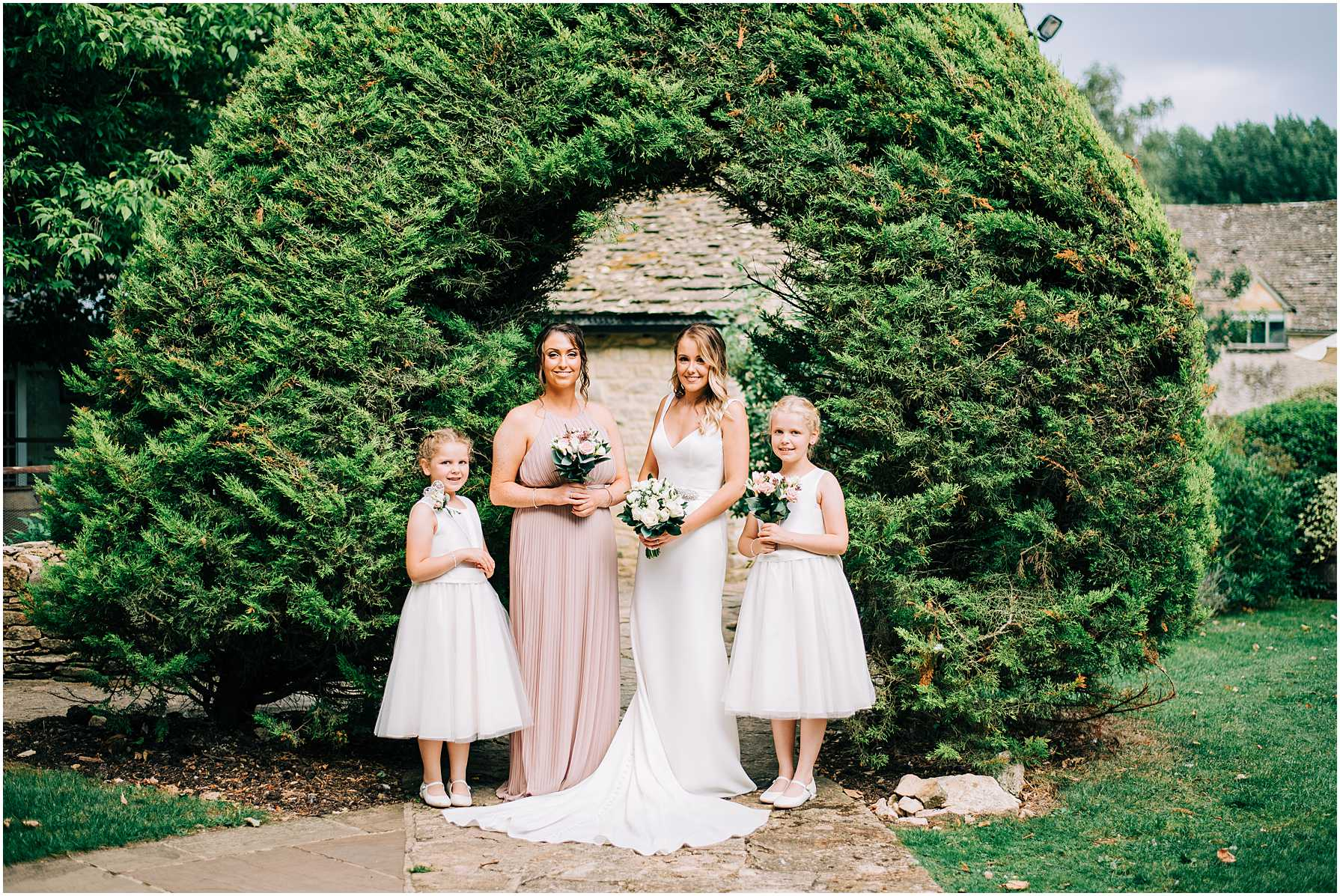 bride and bridesmaids standing in front of an arched tree