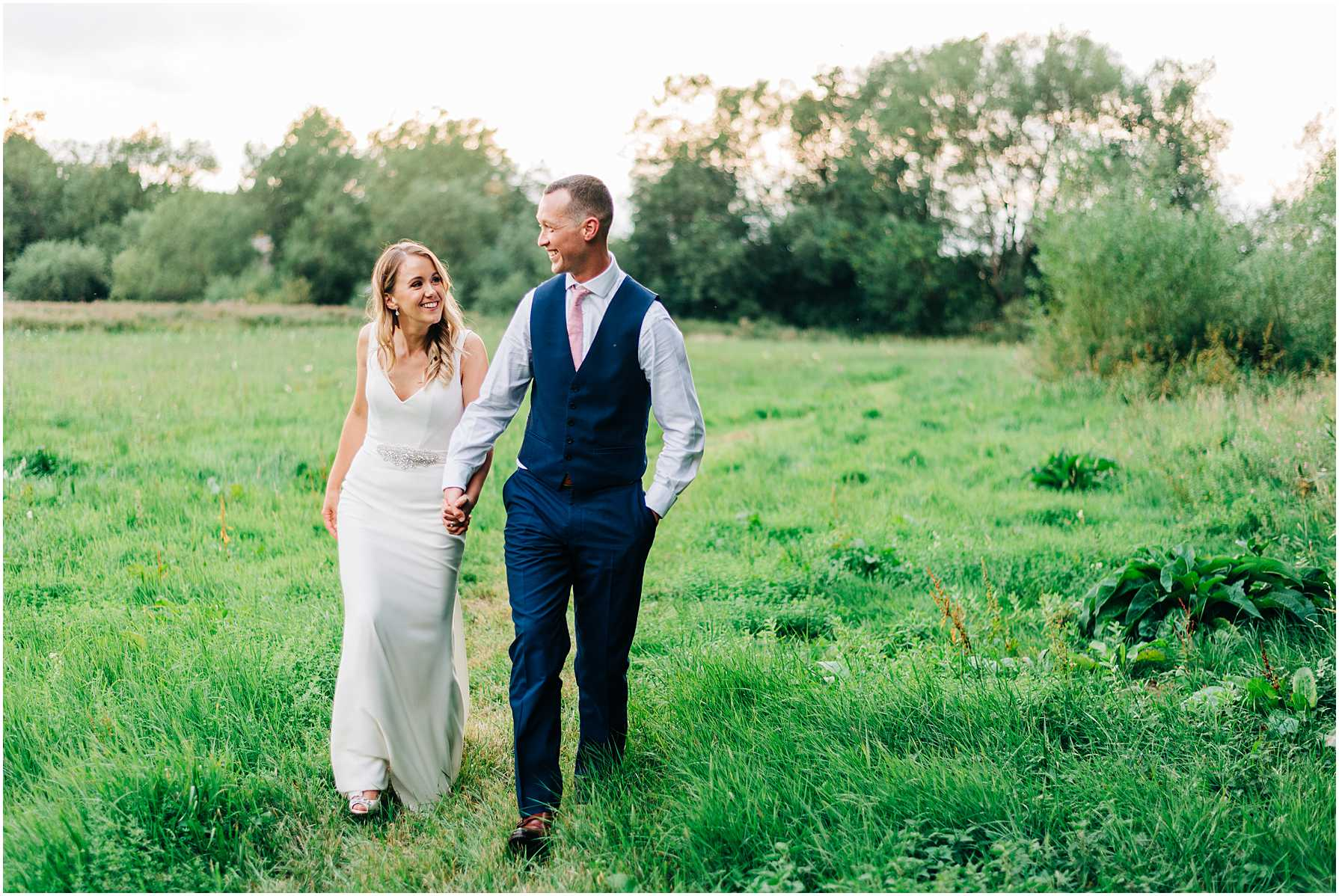 bride and groom walking hand in hand in a field as the sun sets behind them