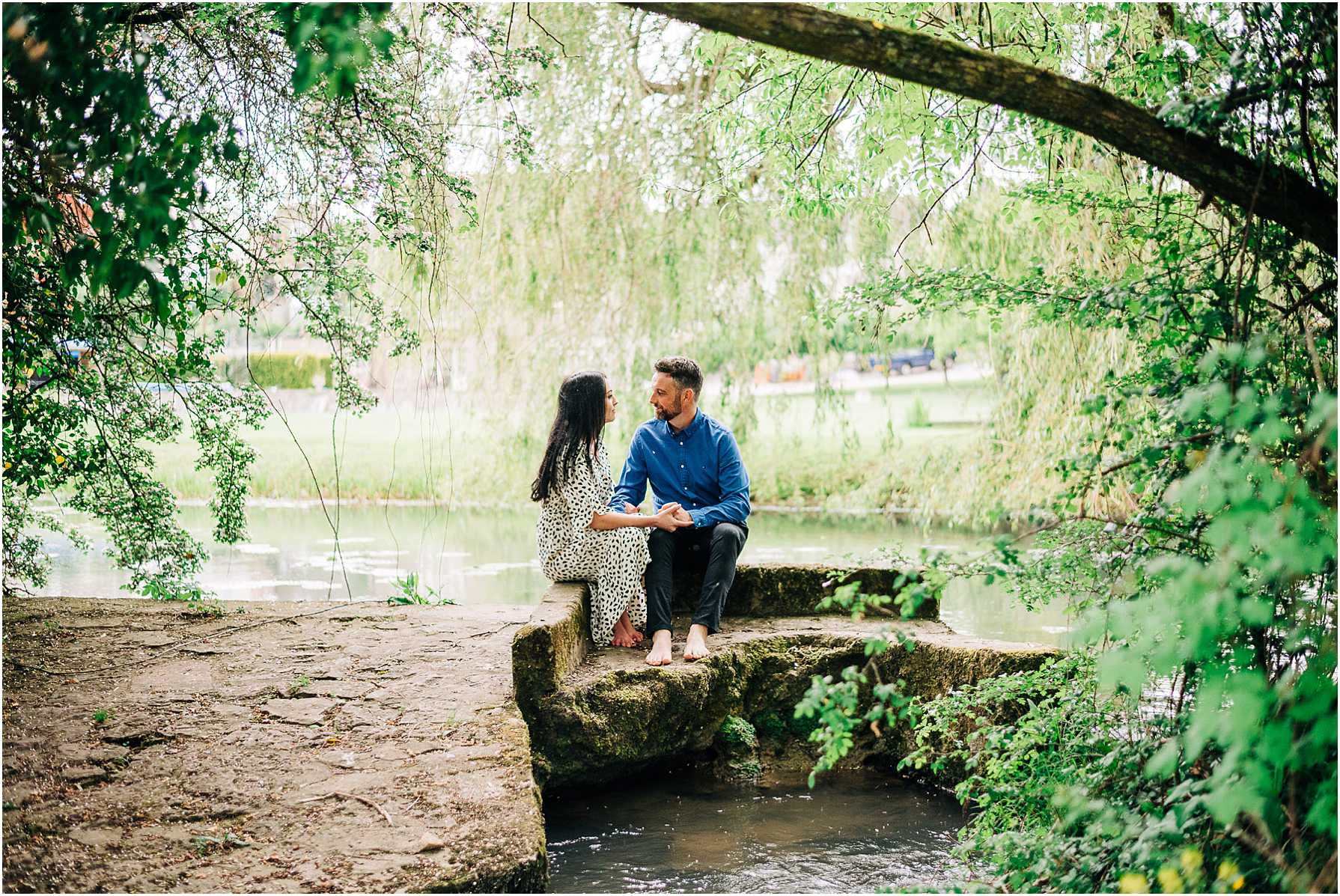couple sitting holding hands under a tree by the river