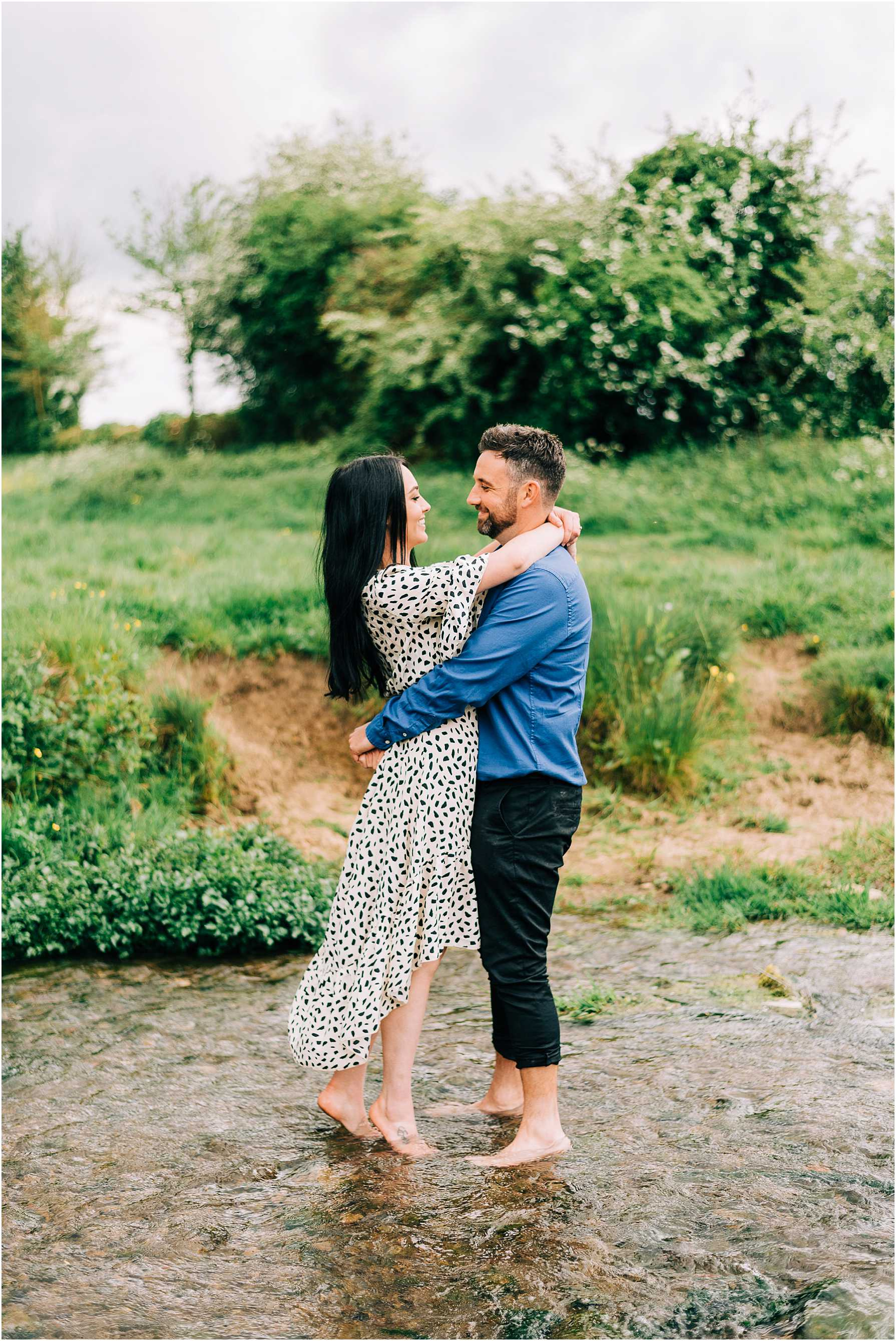 couple standing in a river with their arms around each other