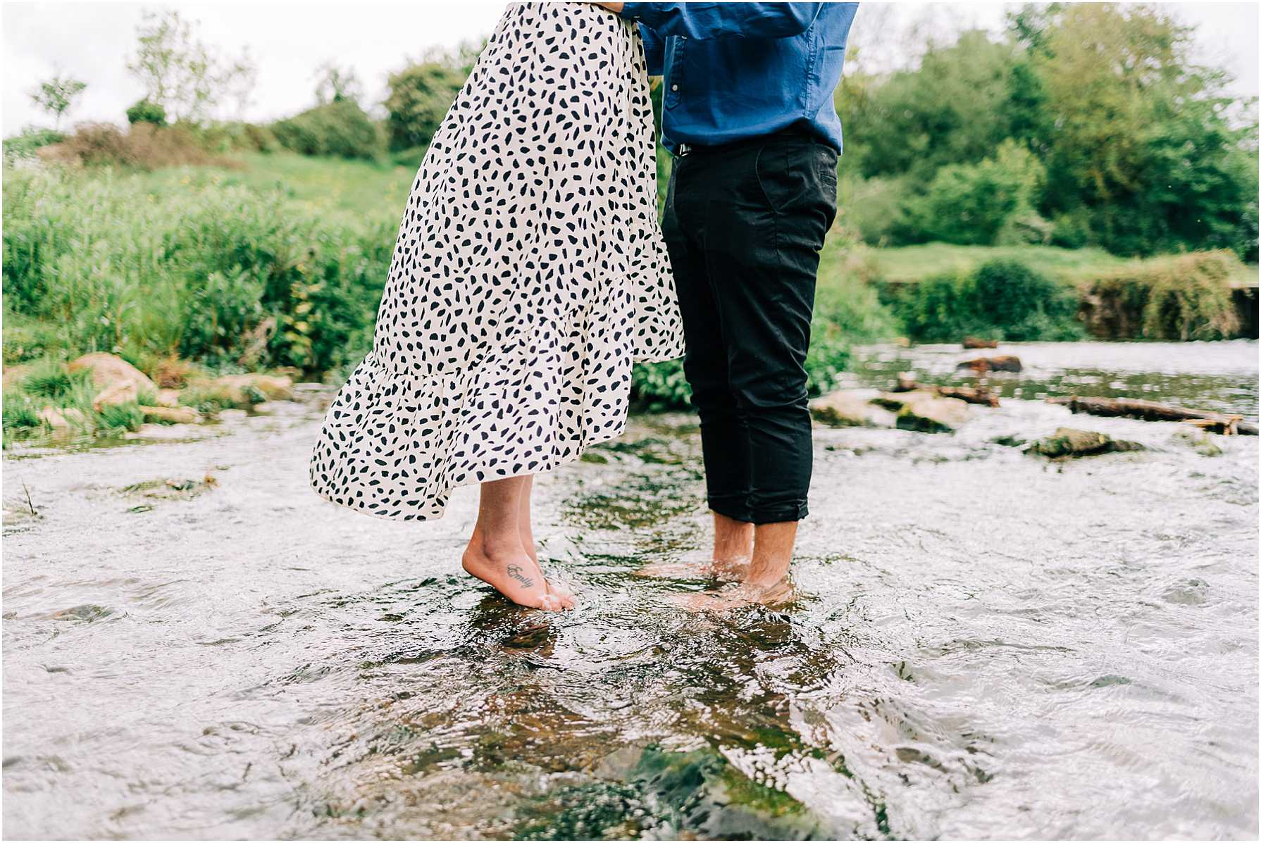 man and woman standing with their feet in a river