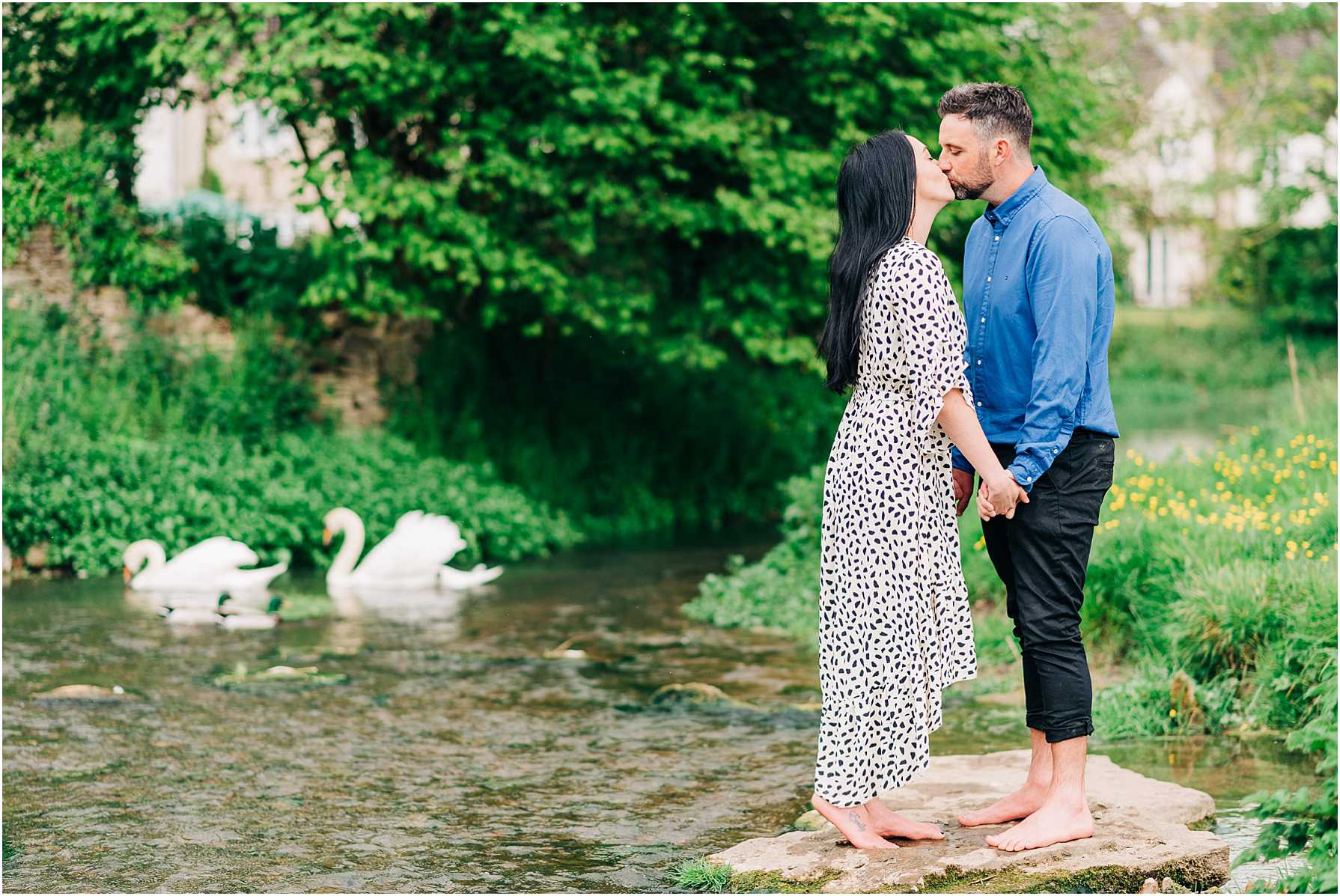 couple standing on a rock in the river kissing with swans in the background