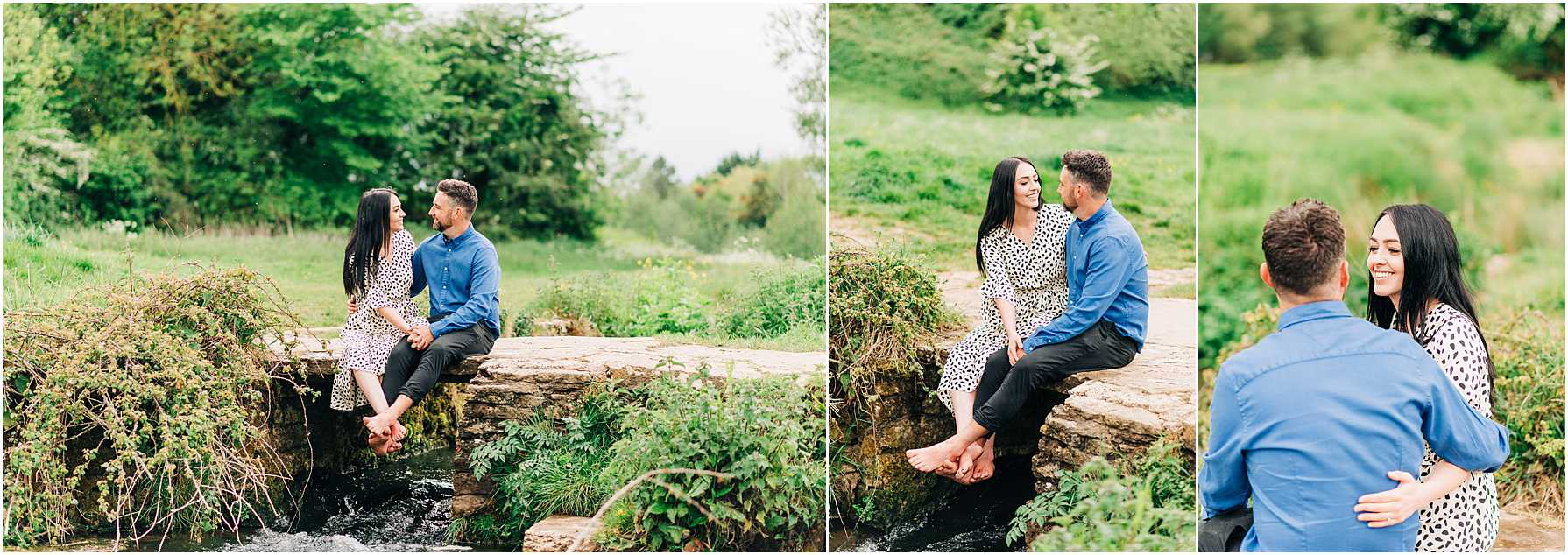 engaged couple sitting on a cobble bridge with their feet hanging over the edge