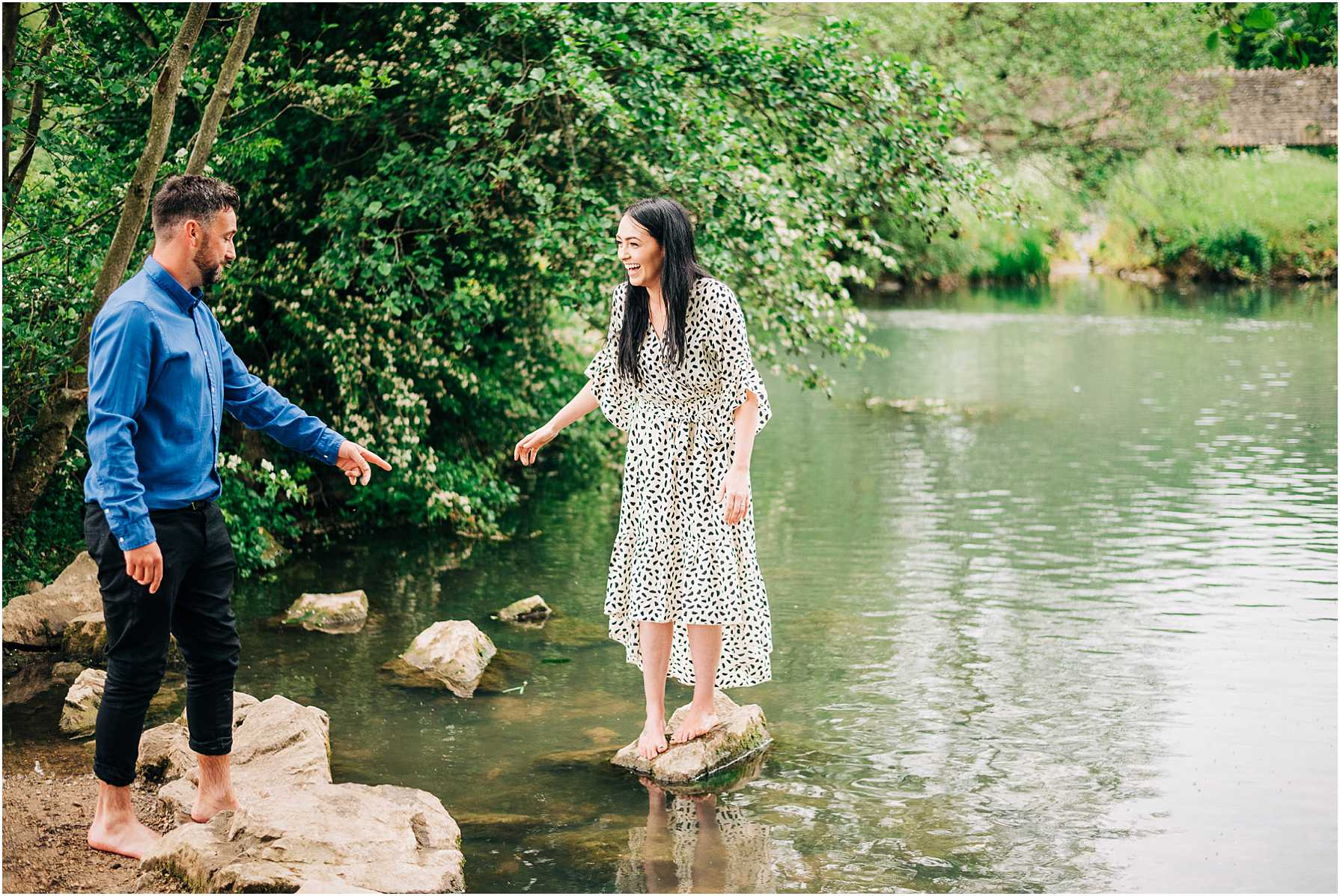man and woman standing on a rock in the river