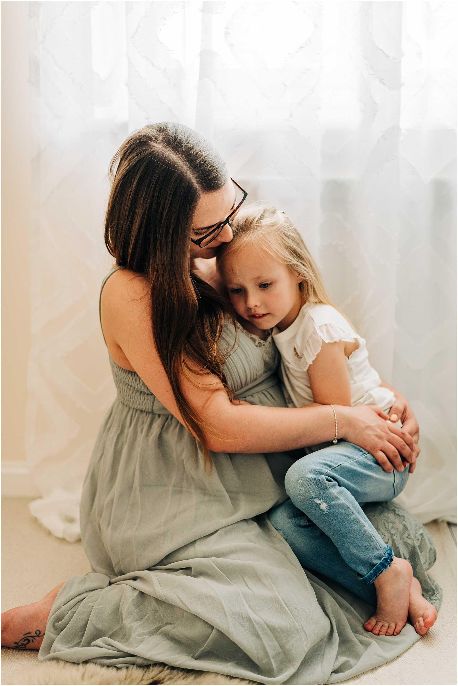 little girl cuddling her mum during a maternity photo shoot