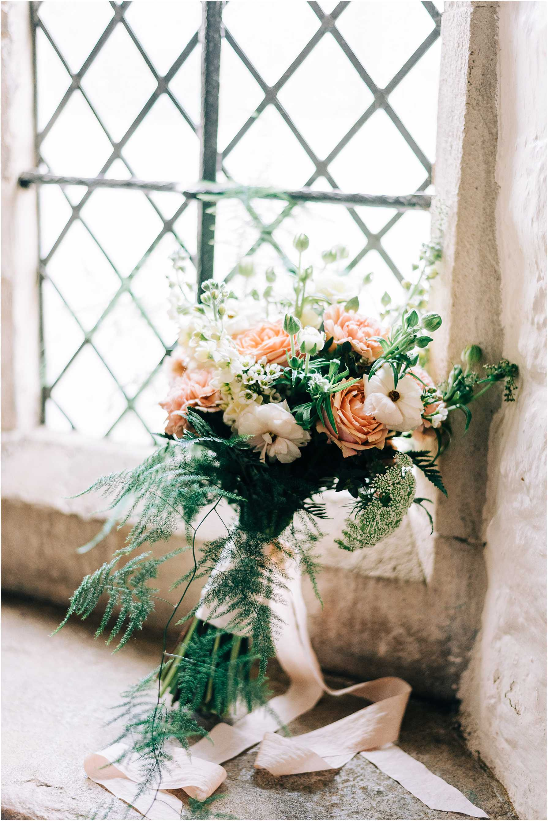 bridal bouquet sitting in a light filled window sill