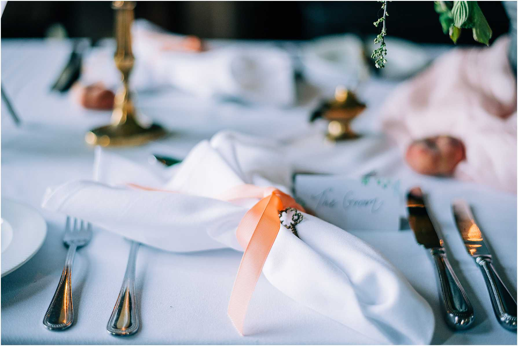 white napkins wrapped with orange ribbon and a small silver key