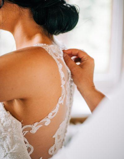 brides mum doing up her dress