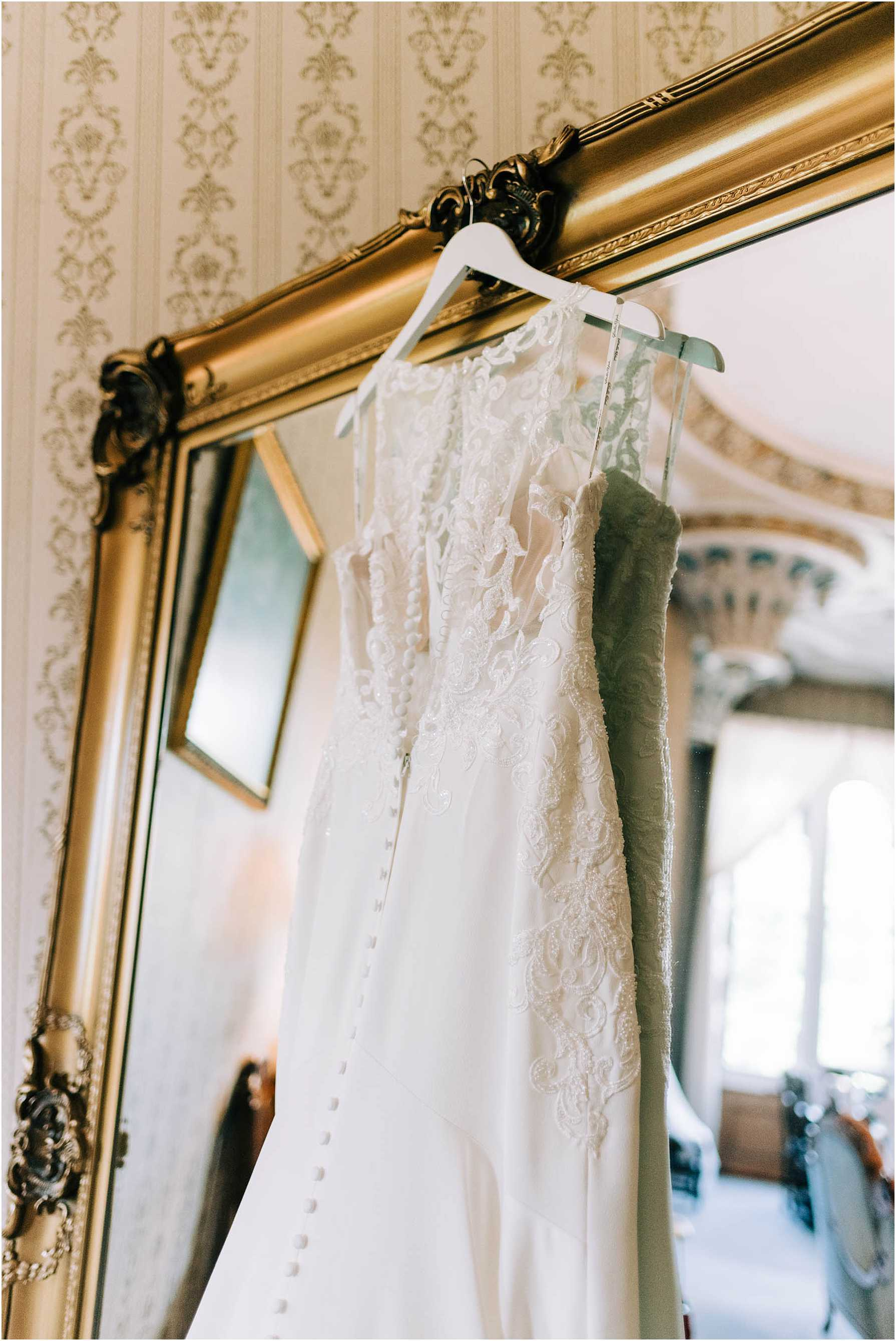 back of brides wedding dress hanging on a mirror