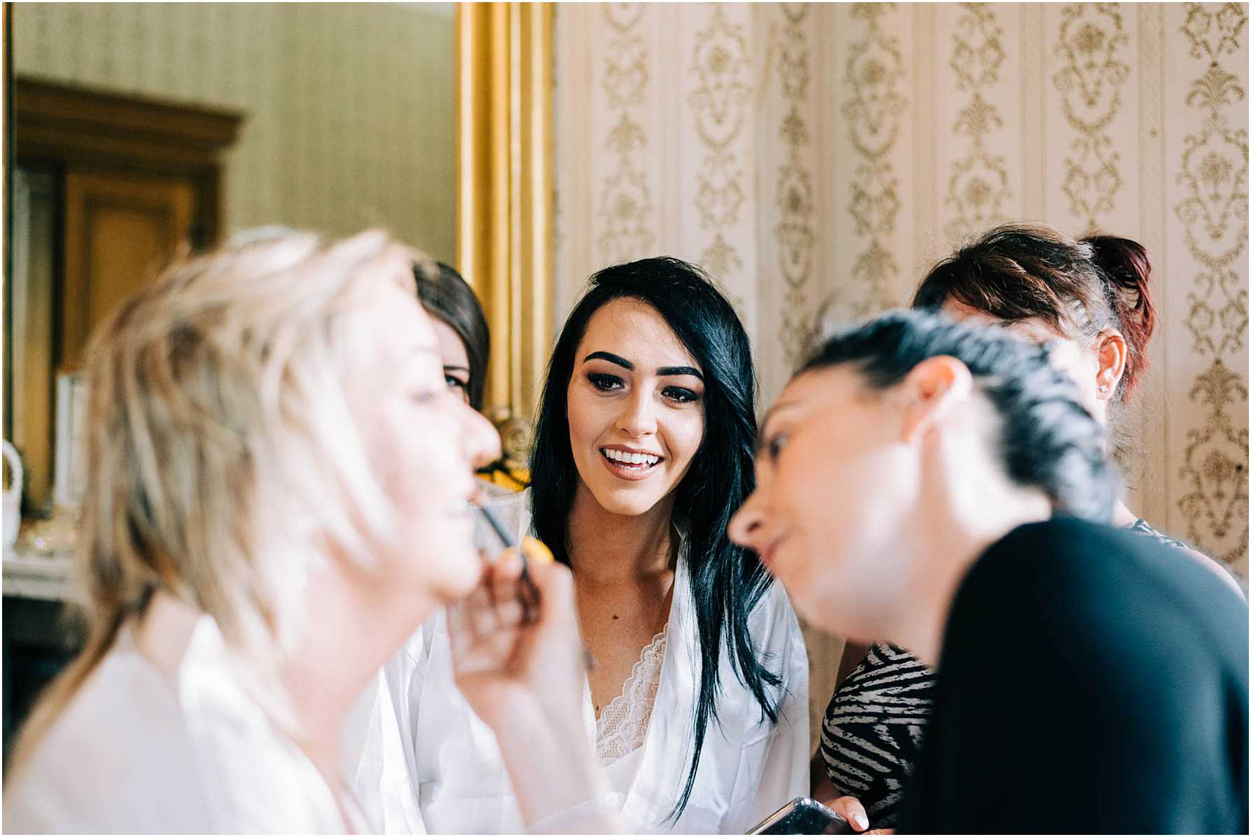 bride and bridesmaid watching mother of the bride having her makeup done