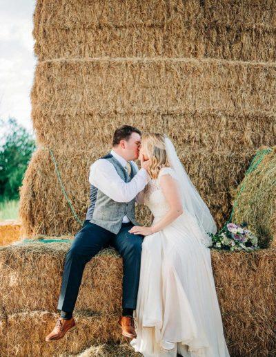 bride and groom sitting on big hay bales