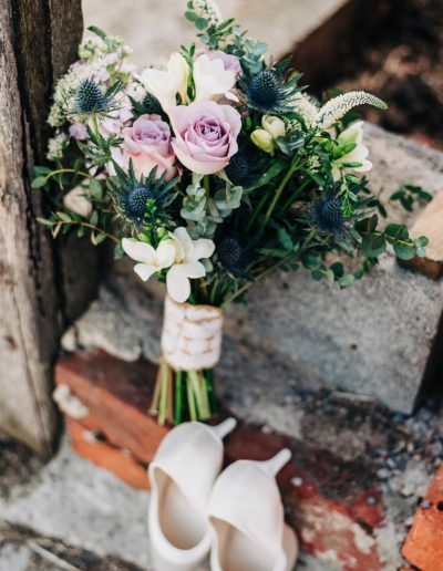 bridal bouquet and wedding shoes on a wall at a farm