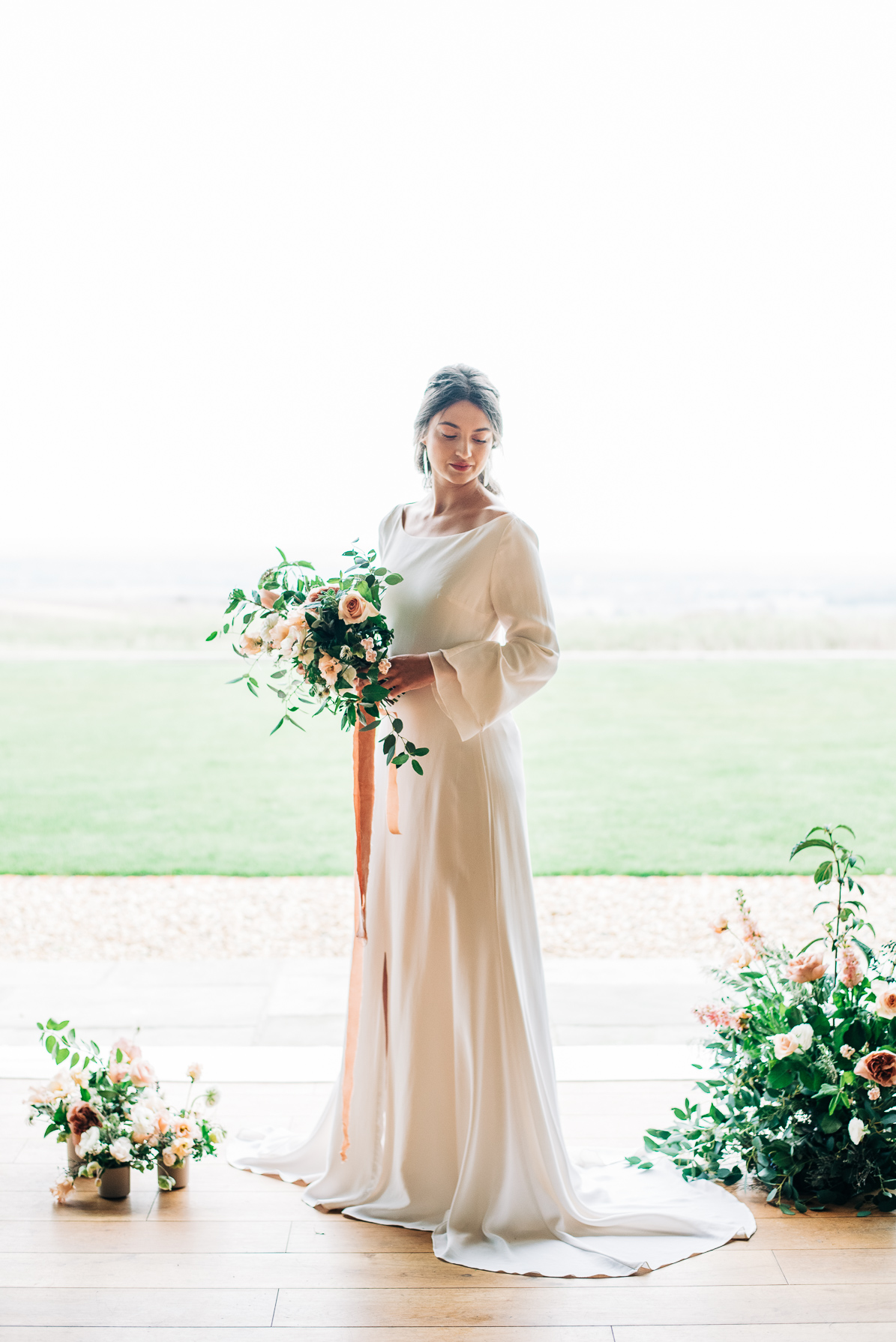 bride stood in doorway holding a bouquet with peach silk ribbon