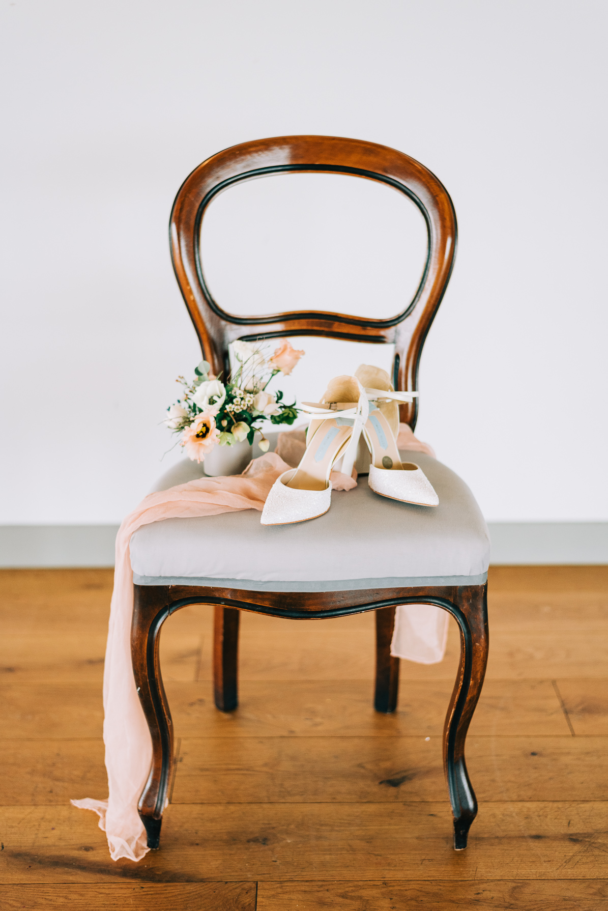 white wedding shoes and play peach silk ribbon on a blue and dark wood chair